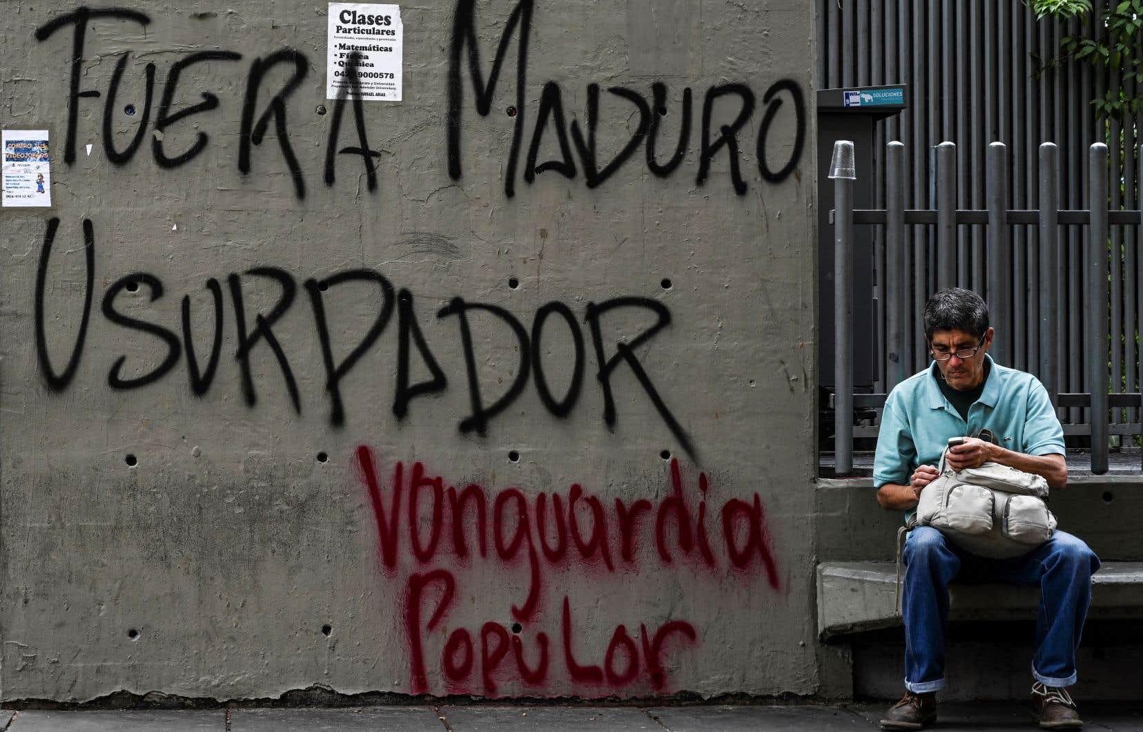 Un homme est assis près d'un graffiti disant «Dehors Maduro l'usurpateur», à Caracas.