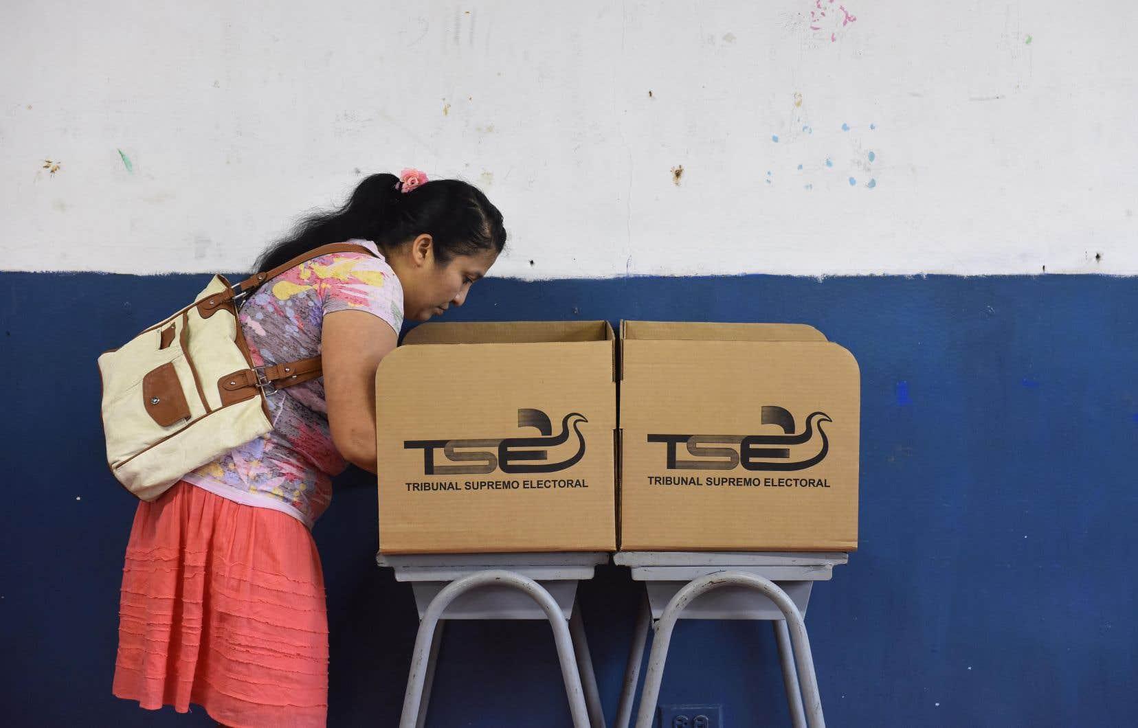 Une femme votant dimanche dans un bureau électoral de la capitale, San Salvador