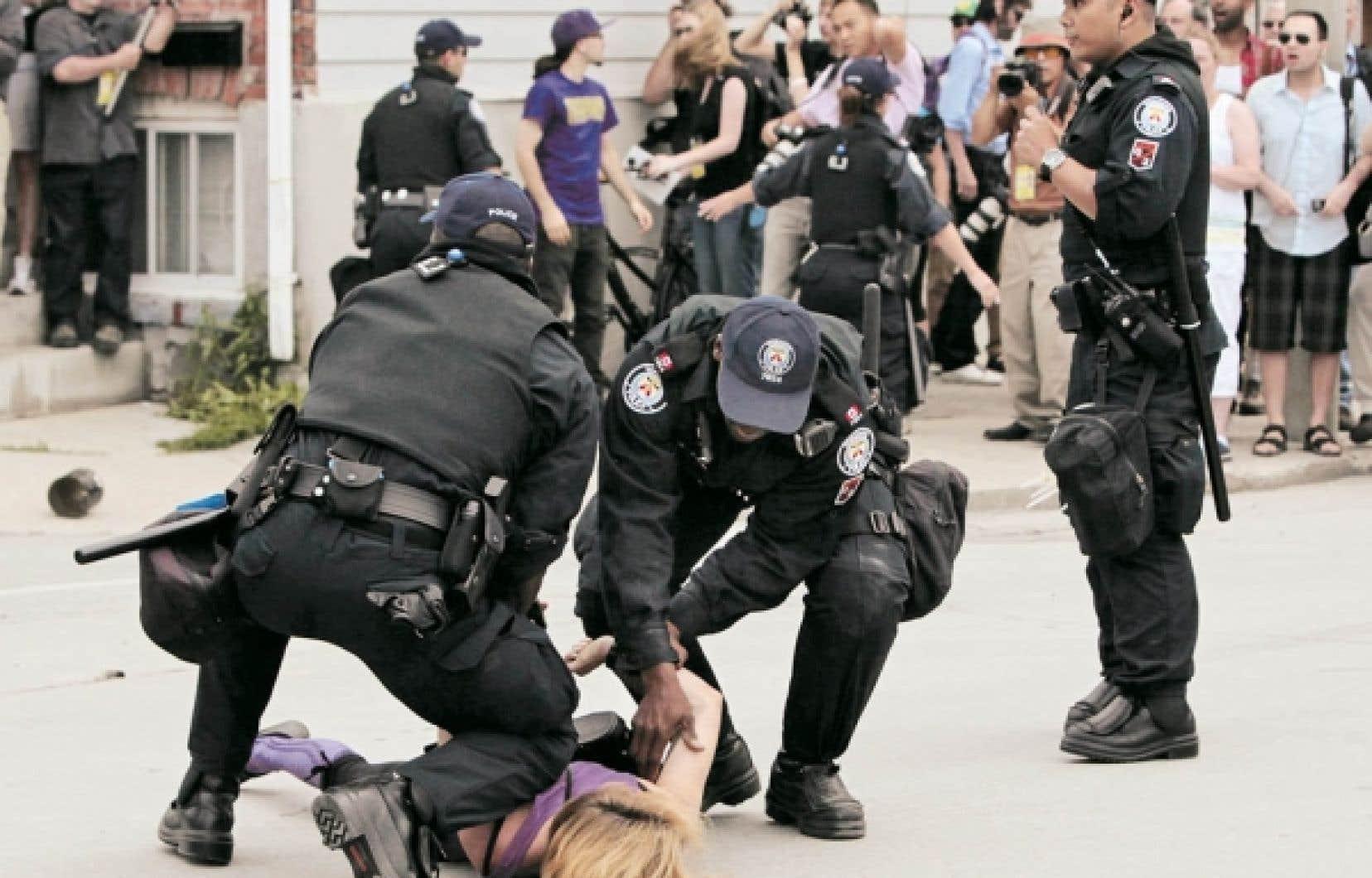 Arrestation d'une jeune femme au cours d'une manifestation au centre-ville de Toronto, dimanche.