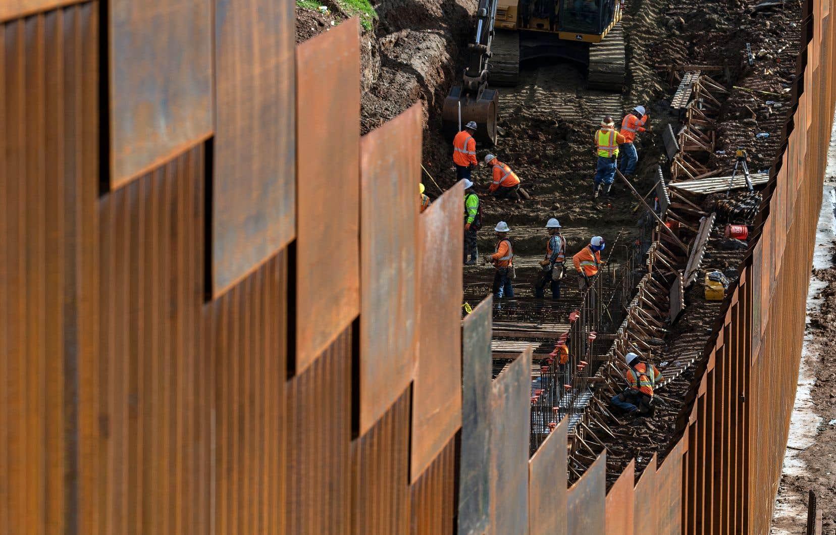 Des travailleurs renforçaient une partie du mur entre les États-Unis et le Mexique, en janvier. Environ un tiers de cette frontière est déjà sécurisé par un mur, des barrières ou des barbelés.