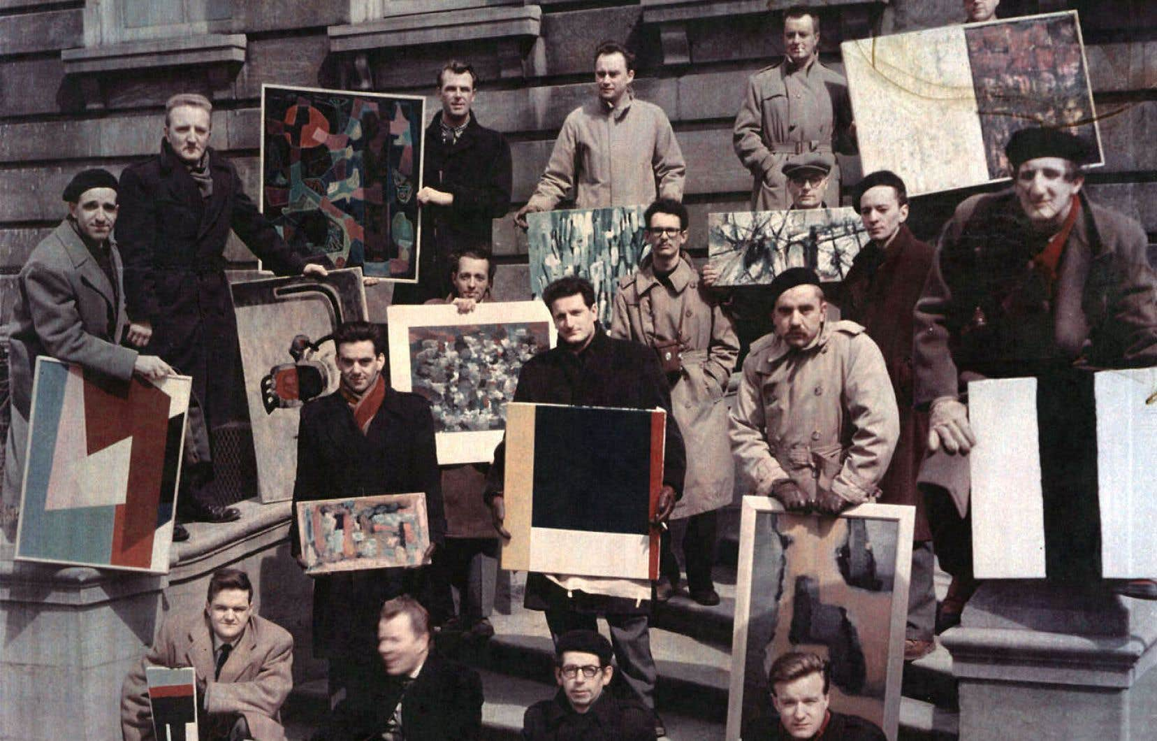 Photo de groupe prise lors d'une exposition de l'Association des artistes non figuratifs de Montréal, organisée au printemps 1957 au YMCA, vue à l'exposition «Hommage aux premiers Plasticiens» tenue à la galerie Simon Blais en 2005. Au premier rang: Louis Belzile, à gauche, et Fernand Toupin, à droite.