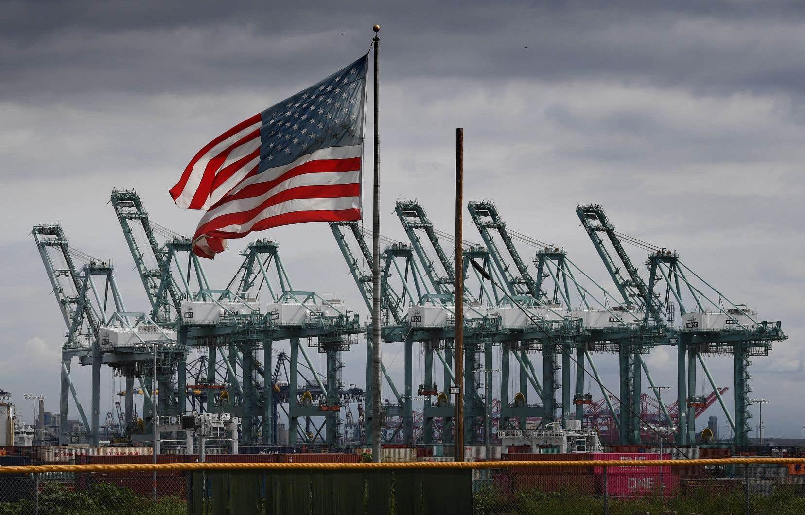 Le drapeau américain flotte au-dessus des grues de transport maritime et des conteneurs à Long Beach, en Californie.