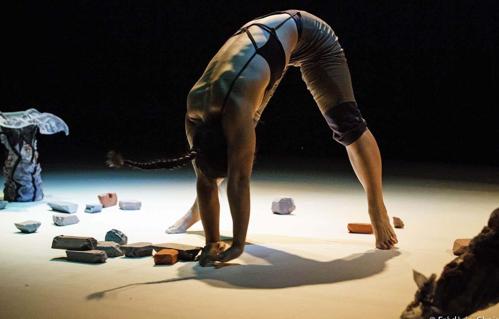 Bailey Engcheminera d'une sculpture à l'autre, laissant voir seulement le travail du dos, dans une posture symbolique de l'animalité.