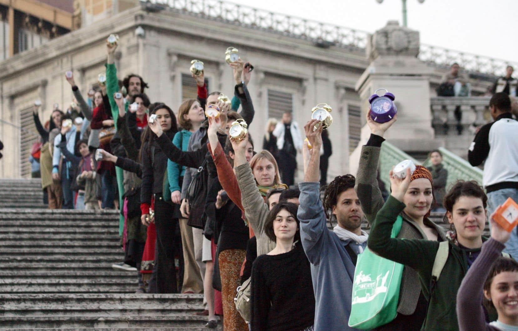 Des personnes brandissaient des réveils qu'elles faisaient sonner sur les marches de la gare Saint-Charles à Marseille, en 2007, lors d'un acte artistique surprise quelques jours avant le printemps et le changement d'heure.