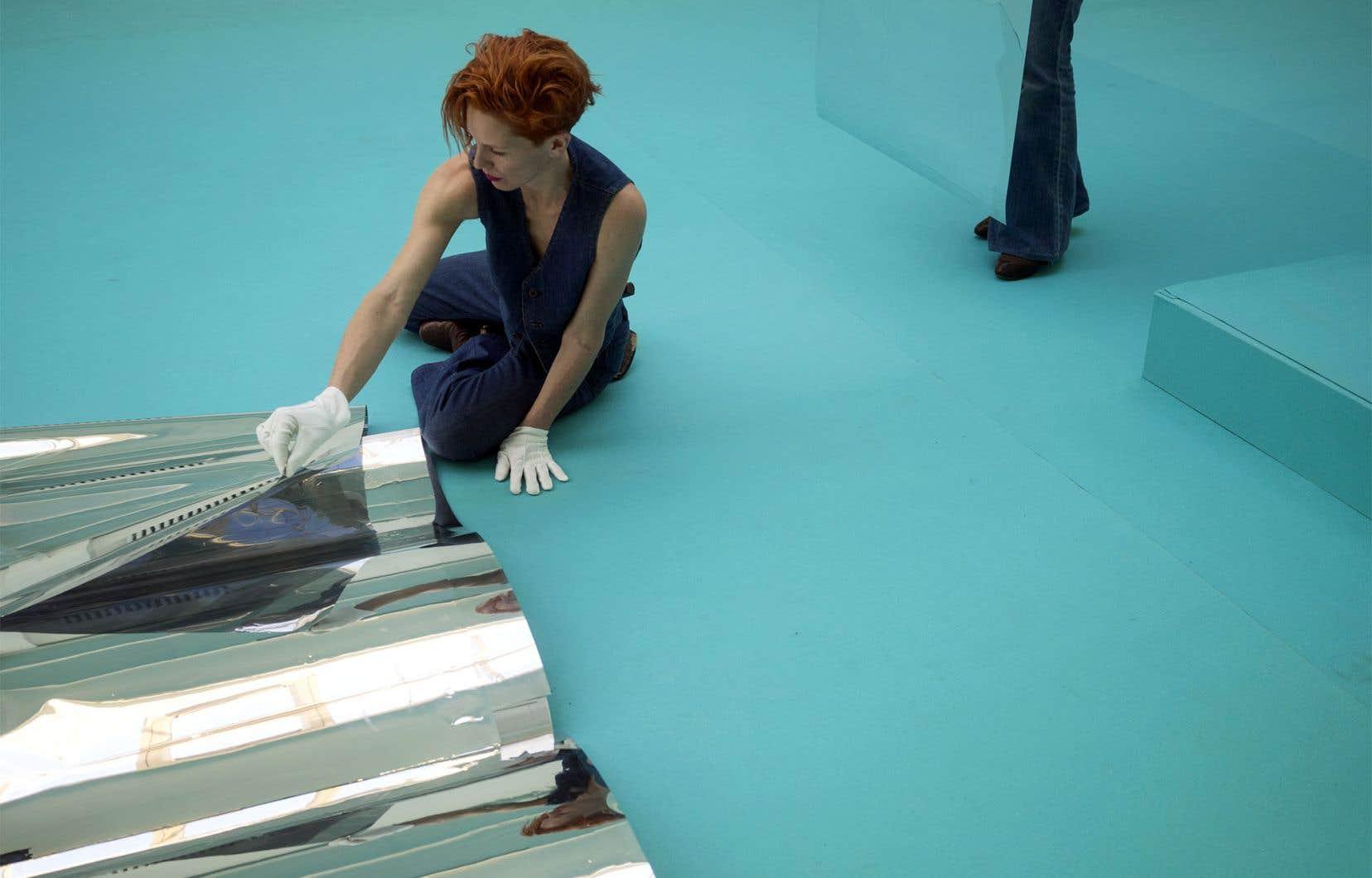 Un premier rituel se répète tandis que chaque interprète vient détacher de larges feuilles miroirs de grands livres ouverts sur le sol et traverse l'espace à reculons.
