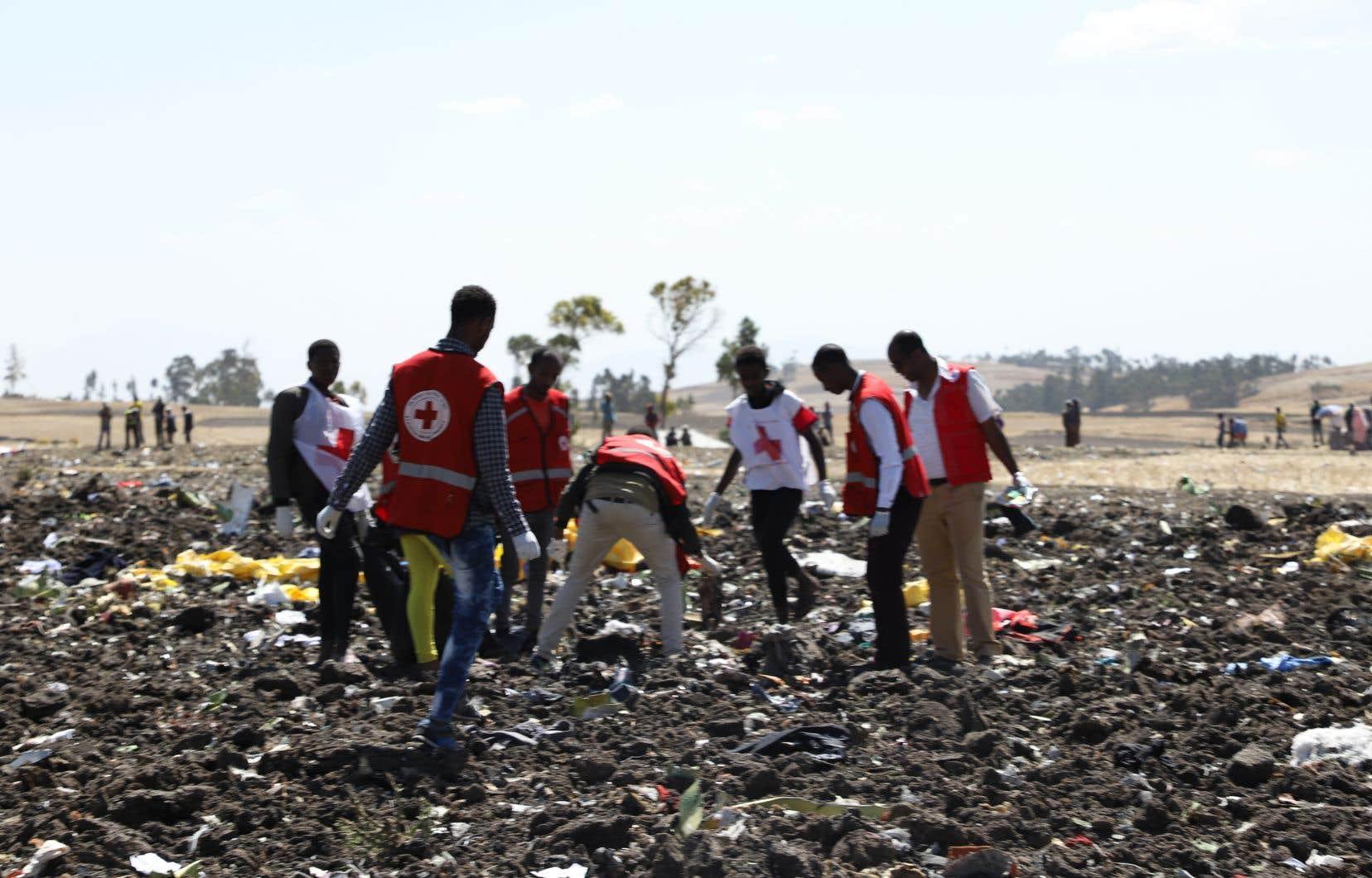 Une équipe de la Croix-Rouge travaille au milieu de débris sur le site de l'écrasement du Boeing 737 d'Ethiopian Airlines près de Bishoftu, une ville située à environ 60 km au sud-est d'Addis-Abeba.