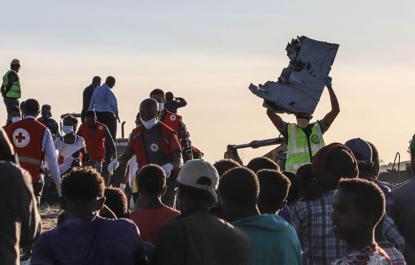 Des personnes s'affairant dans les décombres de l'avion qui s'est écrasé quelques minutes après son décollage.