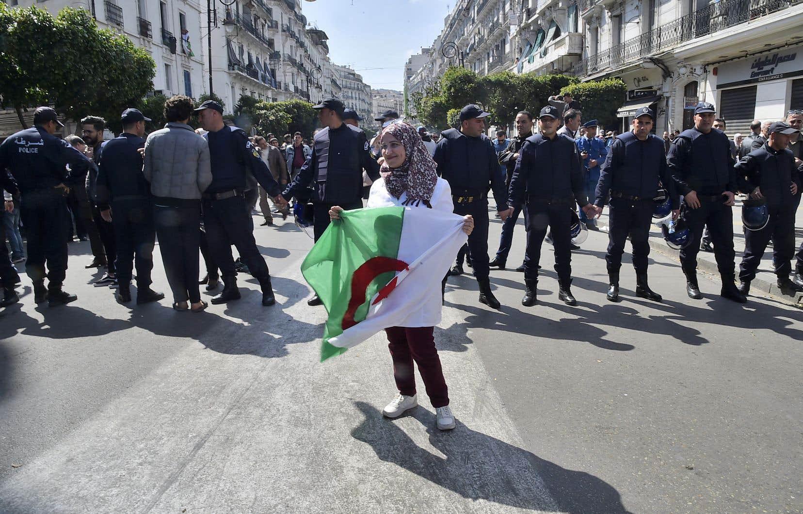 Une professeure algérienne tient le drapeau national au cours d'une manifestation à Alger le 13 mars dernier. Des milliers d'étudiants et de professeurs ont protestécontre la «ruse» d'Abdelaziz Bouteflika afin de se maintenir au pouvoir.