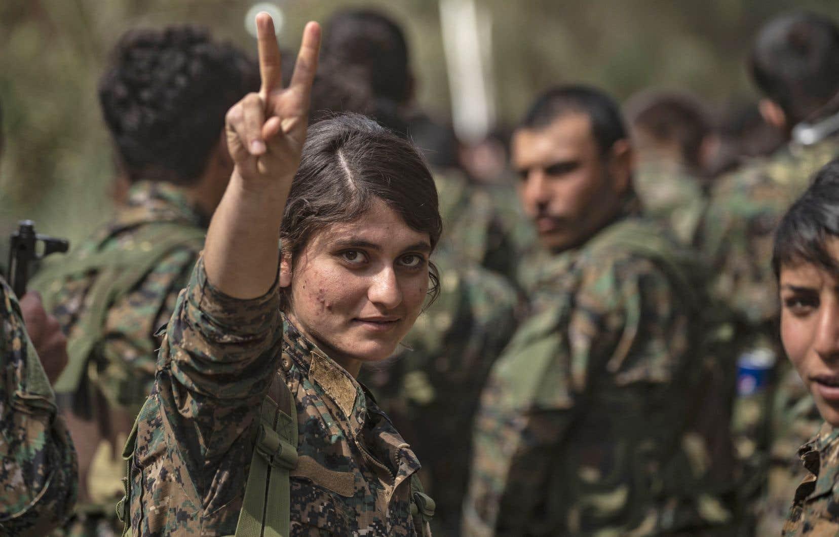 Des combattantes desForces démocratiques syriennes célèbrent la défaite du groupe EIdans la province syrienne de Deir Ezzor, le 23 mars 2019.