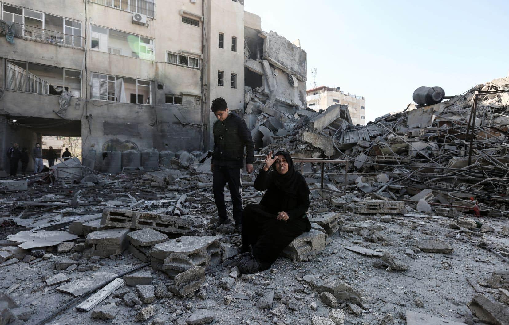 Une Palestinienne assise à côté des décombres d'un bâtiment dans la ville de Gaza.