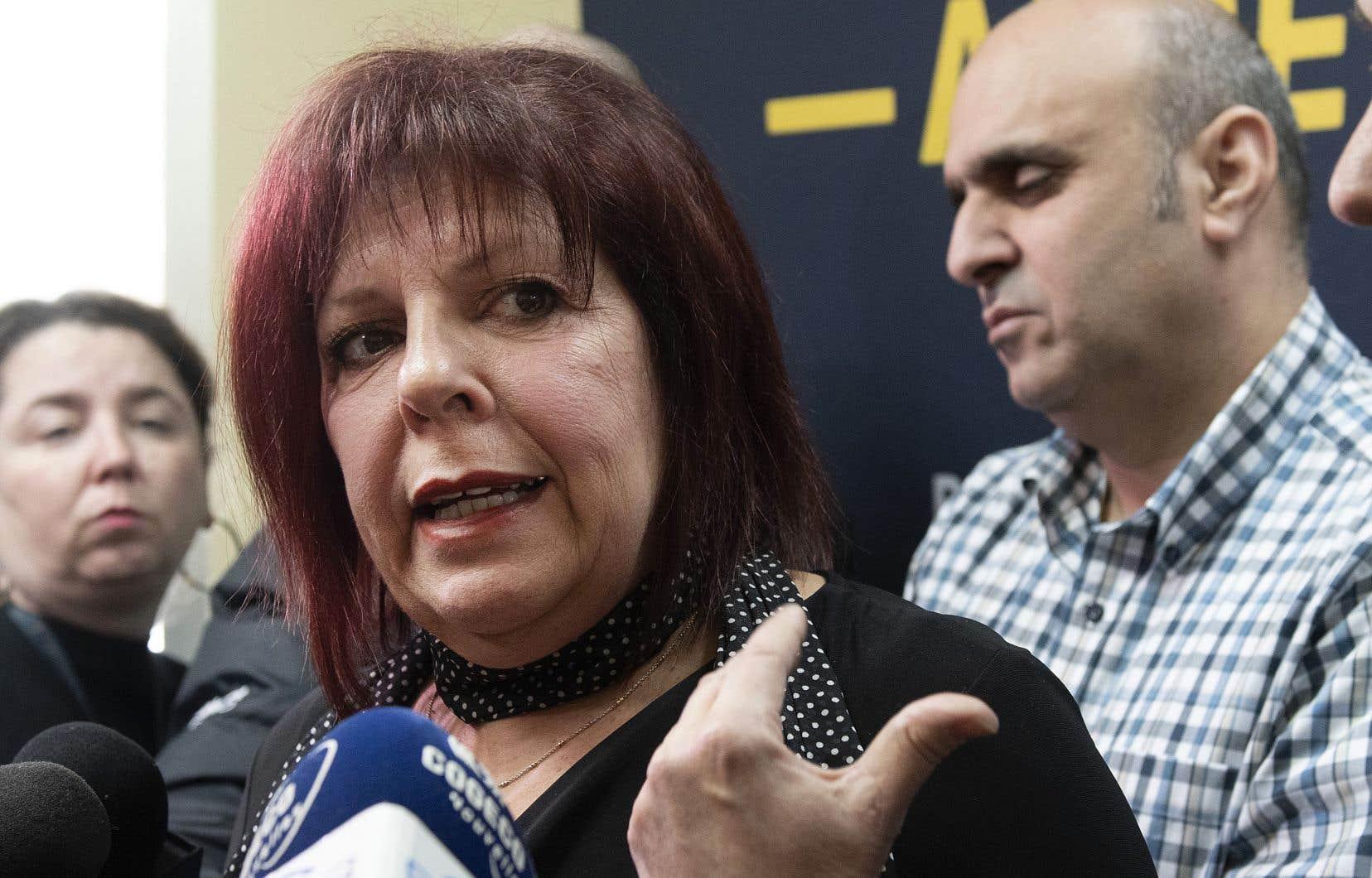 Lynda Poirier, du Centre de prévention du suicide de Québec, répond aux questions des journalistes. Les porte-parole des chauffeurs de taxi, dont Abdallah Homsy, que l'on voit derrière elle, se sont adressés à l'organisme à la suite de deux tentatives de suicide de collègues.