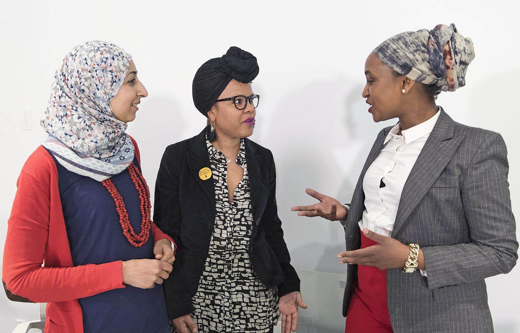 Safa Chebbi, Marlihan Lopez et Idil Issa discutent après la conférence de presse tenue vendredi à Montréal par sept groupes s'opposant au projet de loi sur la laïcité.