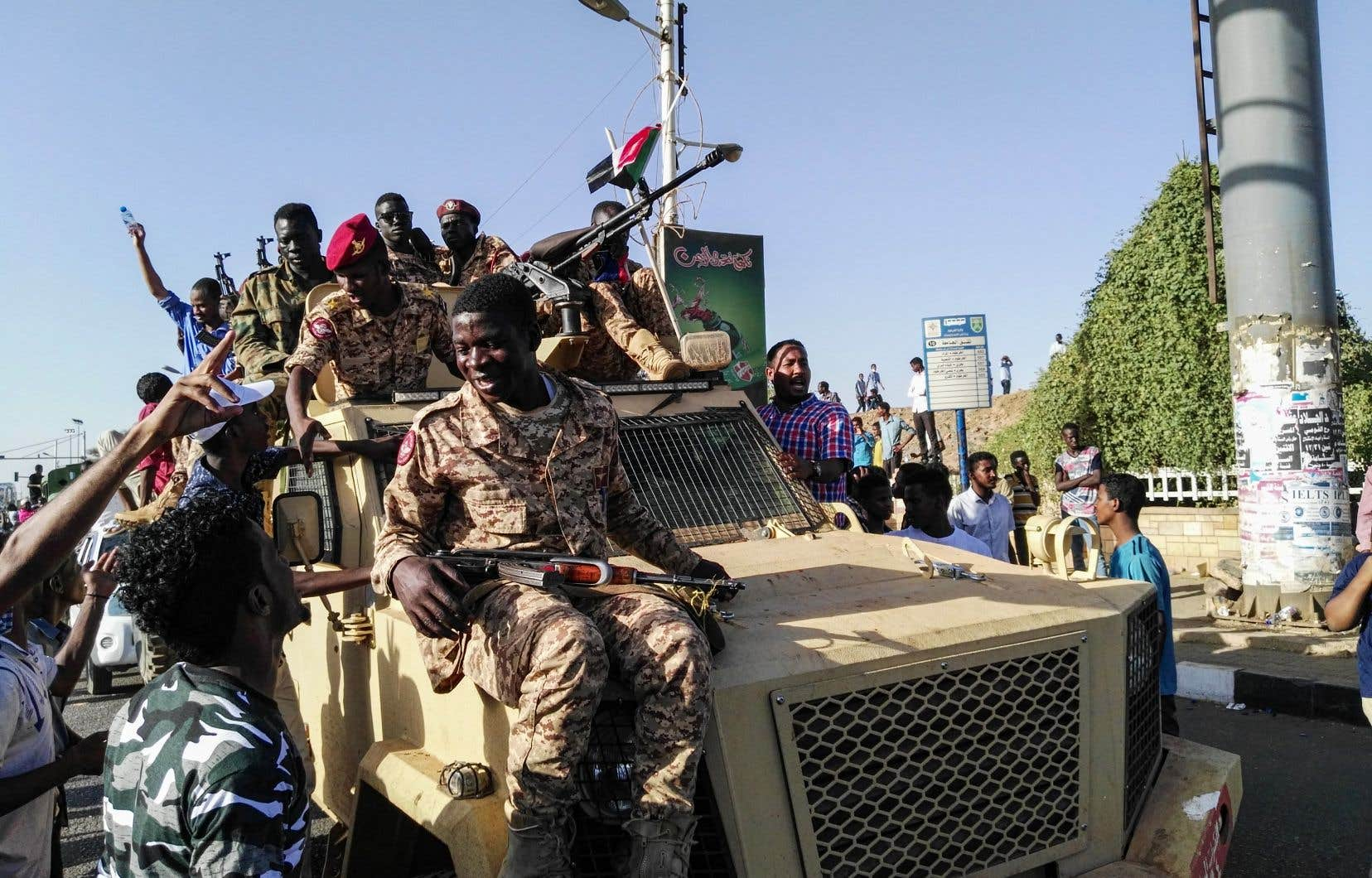Des manifestants grimpent sur un véhicule militaire, aux côtés de soldats, près du quartier général de l'armée à Khartoum, le 7 avril 2019.