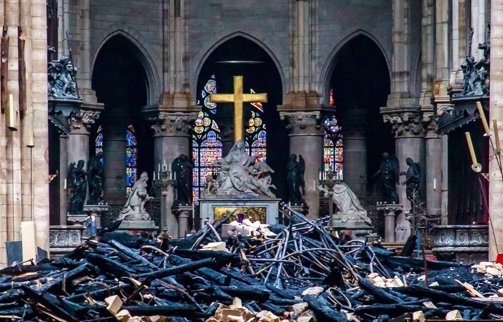 Vue de la nef au fond de laquelle une croix se dresse, épargnée par les morceaux du plafond qui sont tombés tout juste devant.
