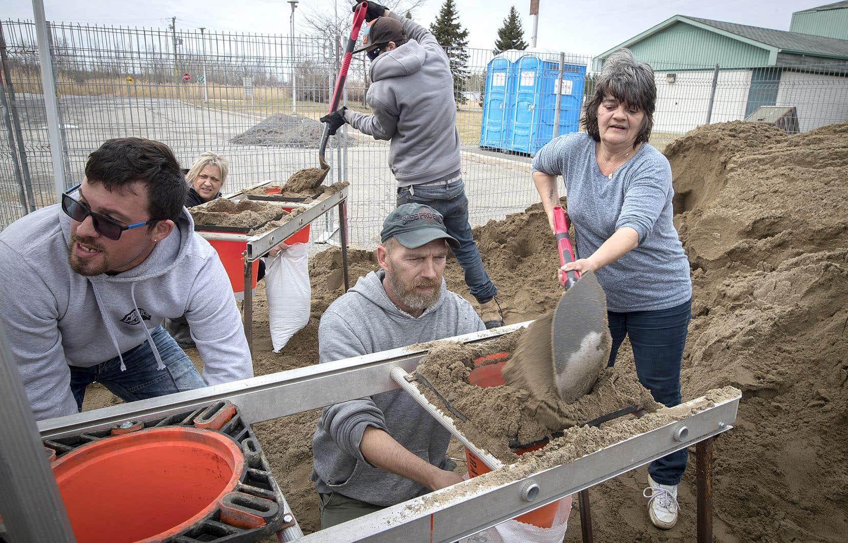 Des résidents de Rigaud ont rempli des sacs de sable en grande quantité, jeudi, pour tenter d'endiguer l'inondation prévue.