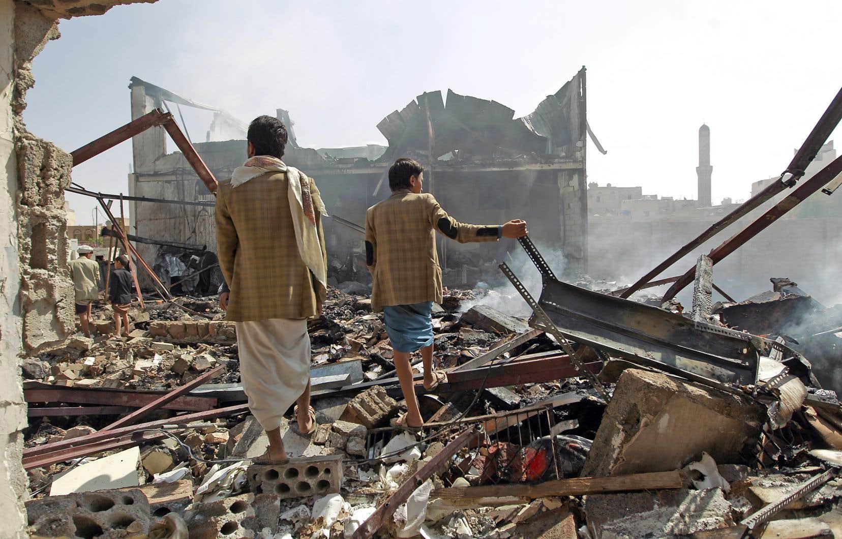 Des travailleurs yéménites regardent la chocolaterie détruite par une attaque aérienne menée par l'armée saoudienne en septembre 2015 dans la capitale Sanaa.