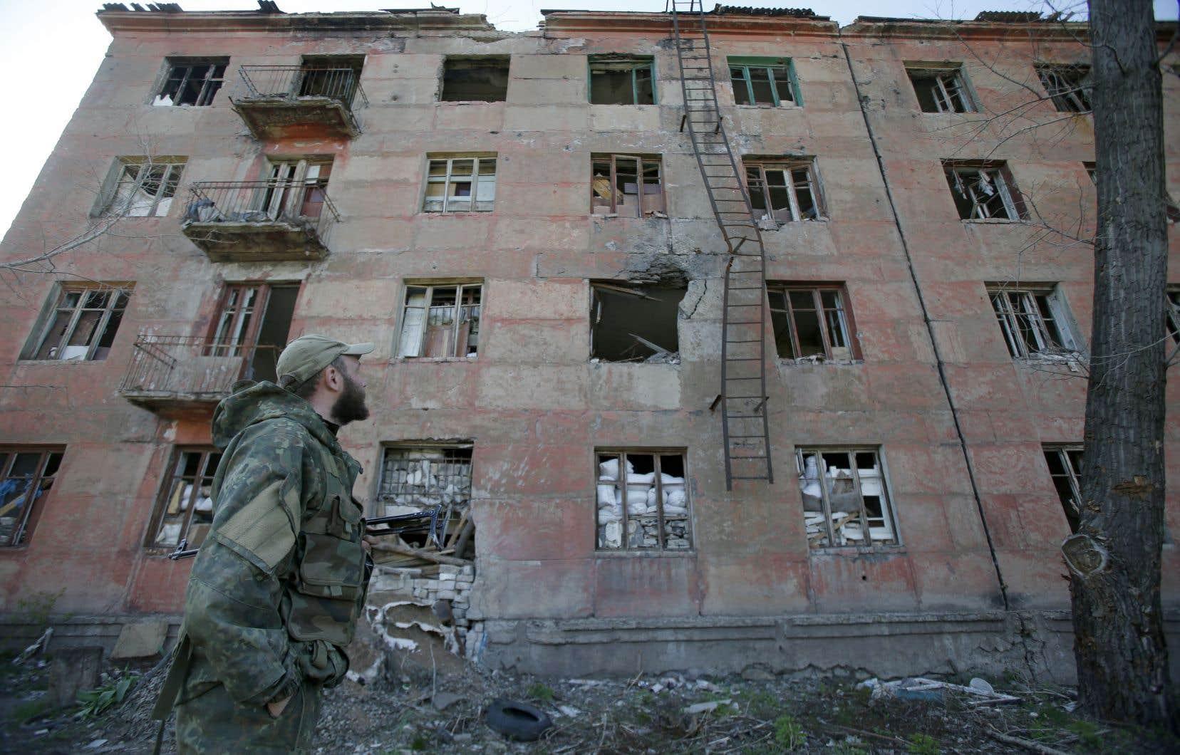 Un militaire ukrainien passe devant un bâtiment détruit à la suite d'un bombardement par des séparatistes soutenus par la Russie dans la petite ville de Zolote, dans la région de Lougansk, le 20 avril 2019.