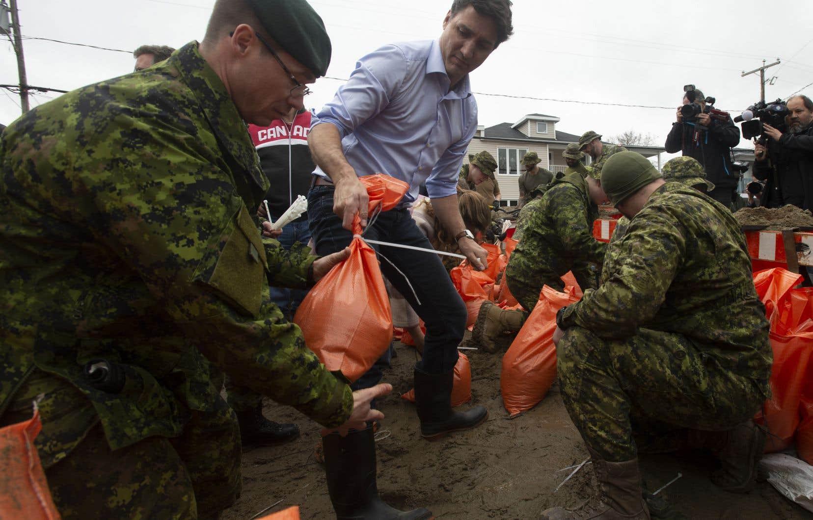 Comme son homologue québécois deux jours plus tôt, le premier ministre a rempli quelques sacs de sable avec des soldats.