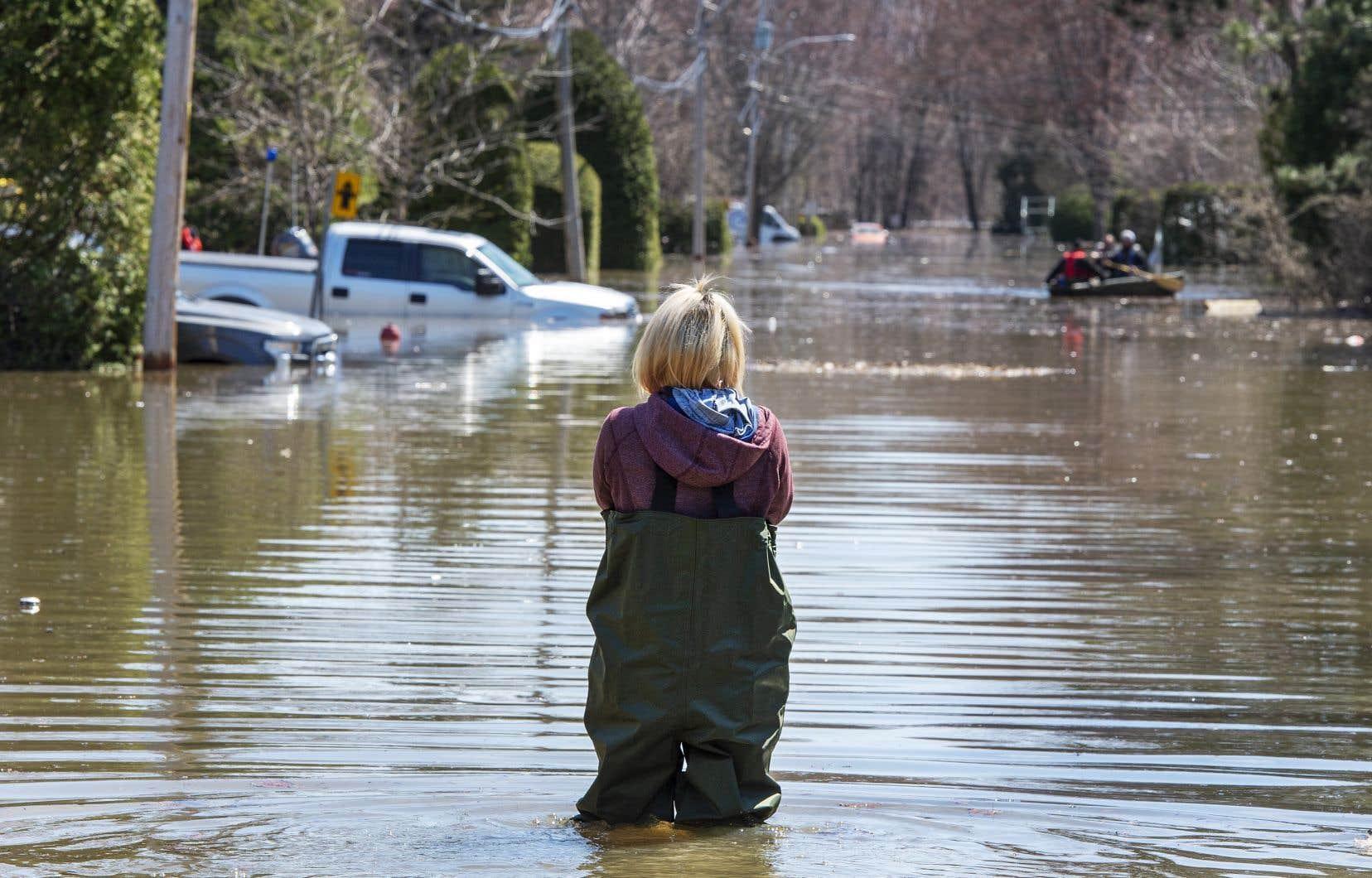 Une résidente de Sainte-Marthe-sur-le-Lac regarde la rue qu'elle habite envahie par l'eau.