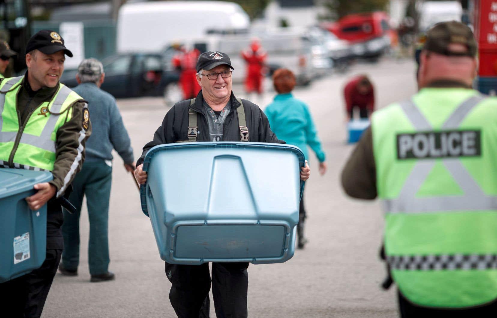 Escorté et aidé par un policier, un sinistré de Sainte-Marthe-sur-le-Lac transporte des effets personnels qu'il a pu aller chercher dans sa résidence inondée.