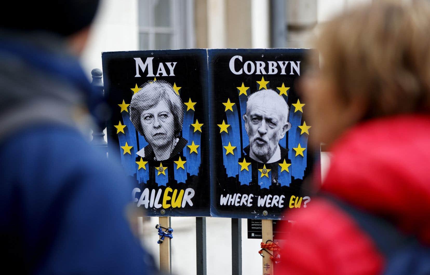 Des piétons passent devant des pancartes montrant la première ministre britannique, Theresa May, et le chef du Parti travailliste, Jeremy Corbyn, près du parlement, dans le centre de Londres, le 3 avril 2019.