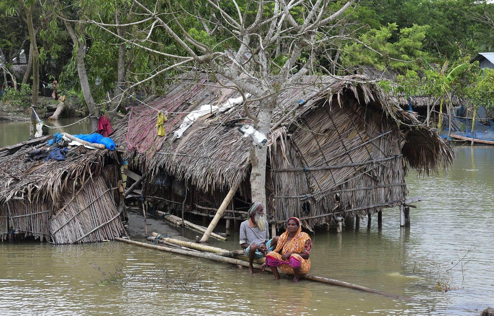 Un couple de personnes âgées en détresse assises sur un tronc d'arbre près de chez elles, le 4 mai 2019, à Khulna, lorsque le cyclone «Fani» a atteint le Bangladesh