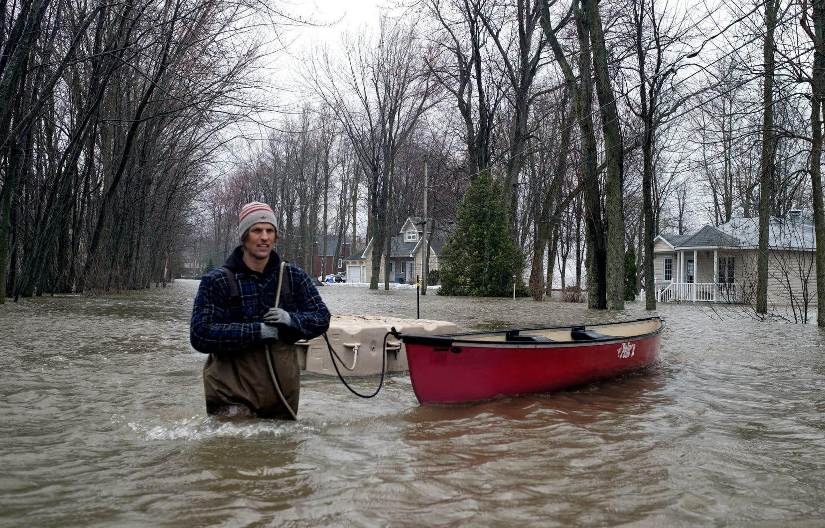 Un citoyen sinistré tire des embarcations dans une rue inondée de Saint-André-d'Argenteuil au plus fort de la crue, à la fin avril.