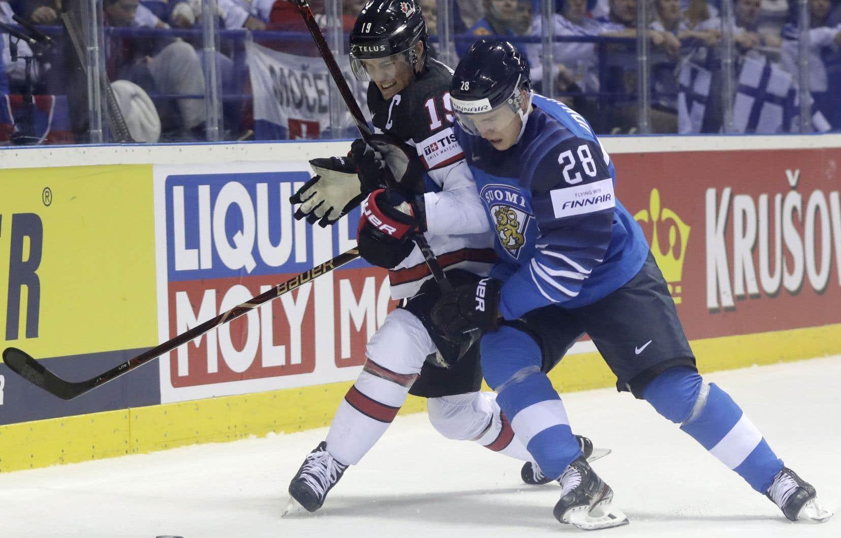 Kyle Turris, du Canada, et Henri Jokiharju, de la Finlande, bataillent pour la rondelle dans le premier match des deux équipes au Championnat du monde disputé en Slovaquie.