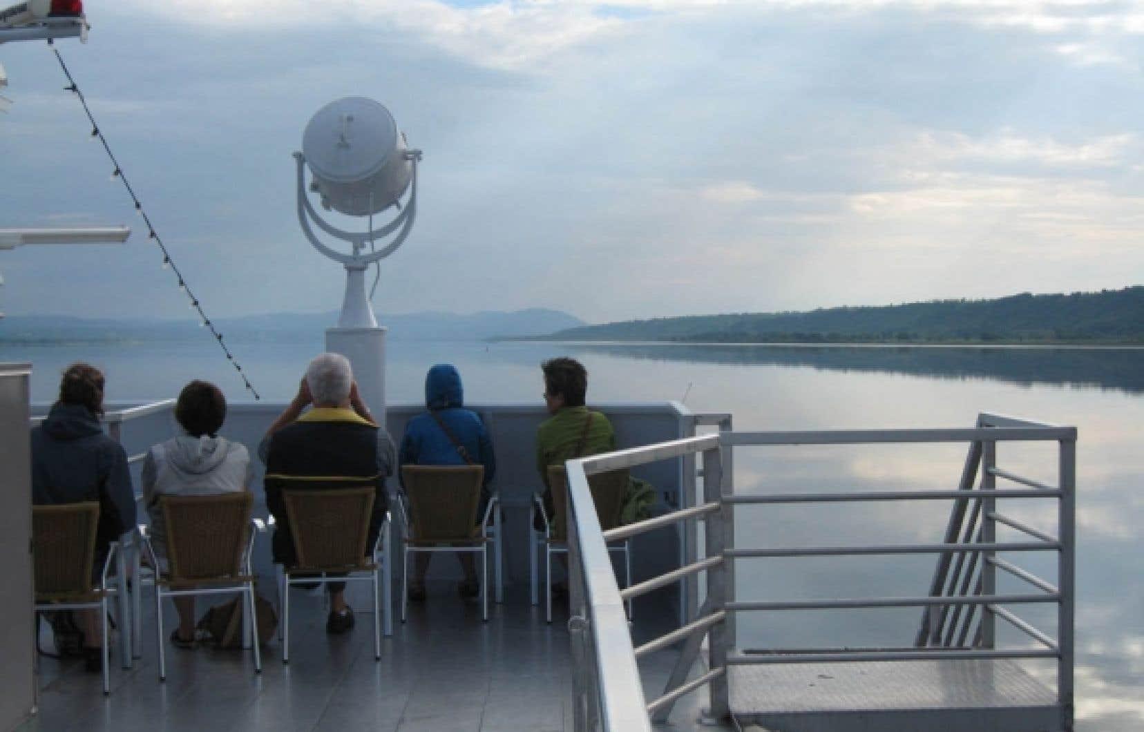 Des passagers observent le fleuve, au bout de l'Ile d'Orléans. <br />