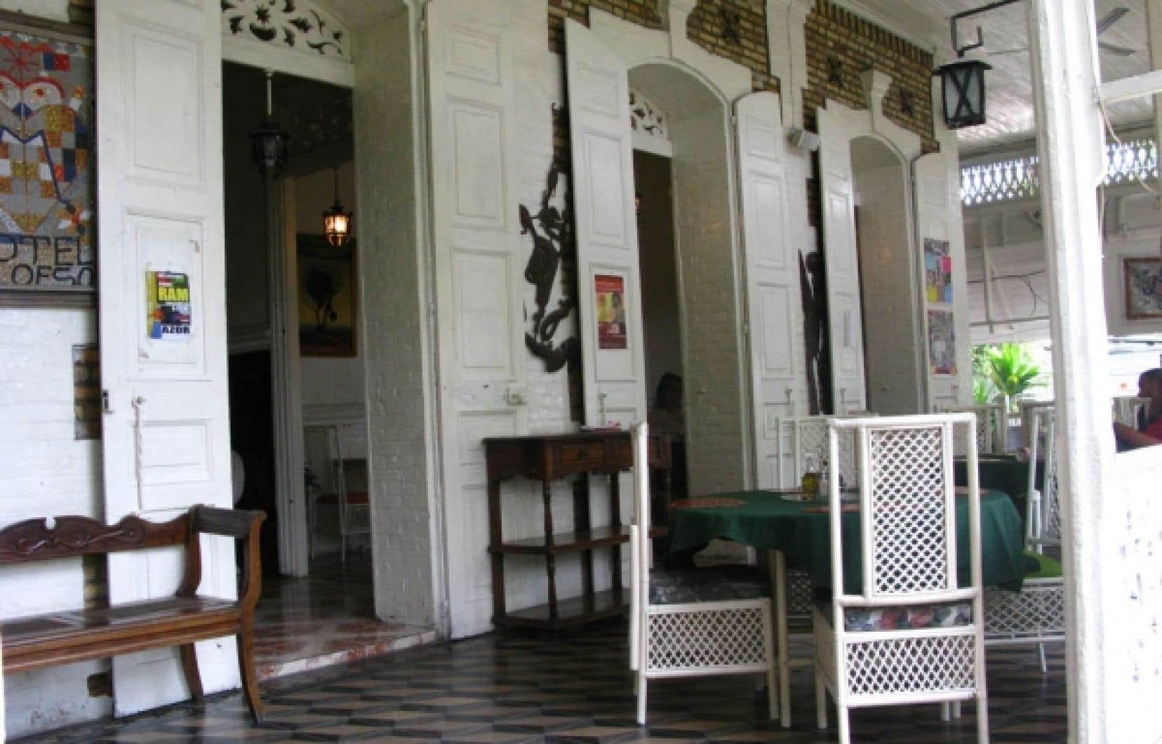 La véranda de l'hôtel Oloffson, dont le charme irrésistible continue de pourvoir aux besoins de l'amateur de bonne chère et du voyageur curieux de traditions locales, et d'attirer une clientèle intellectuelle haïtienne. <br />