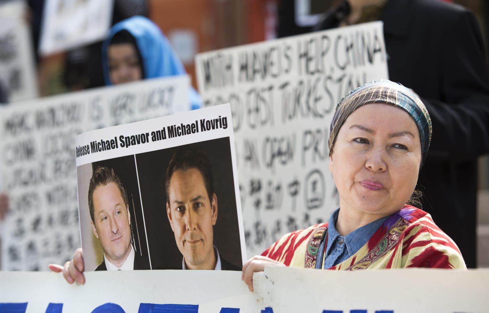 Des manifestants brandissent des photos de Michael Spavor et Michael Kovrig lors d'un rassemblement à Vancouver.