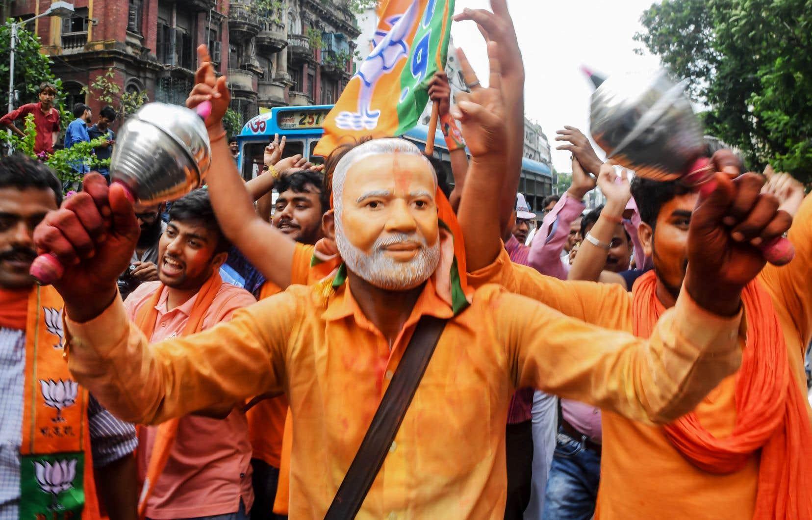 Des partisans du parti du premier ministre indien Narendra Modi célèbrent l'annonce des premiers résultats électoraux dans les rues de Kolkata.