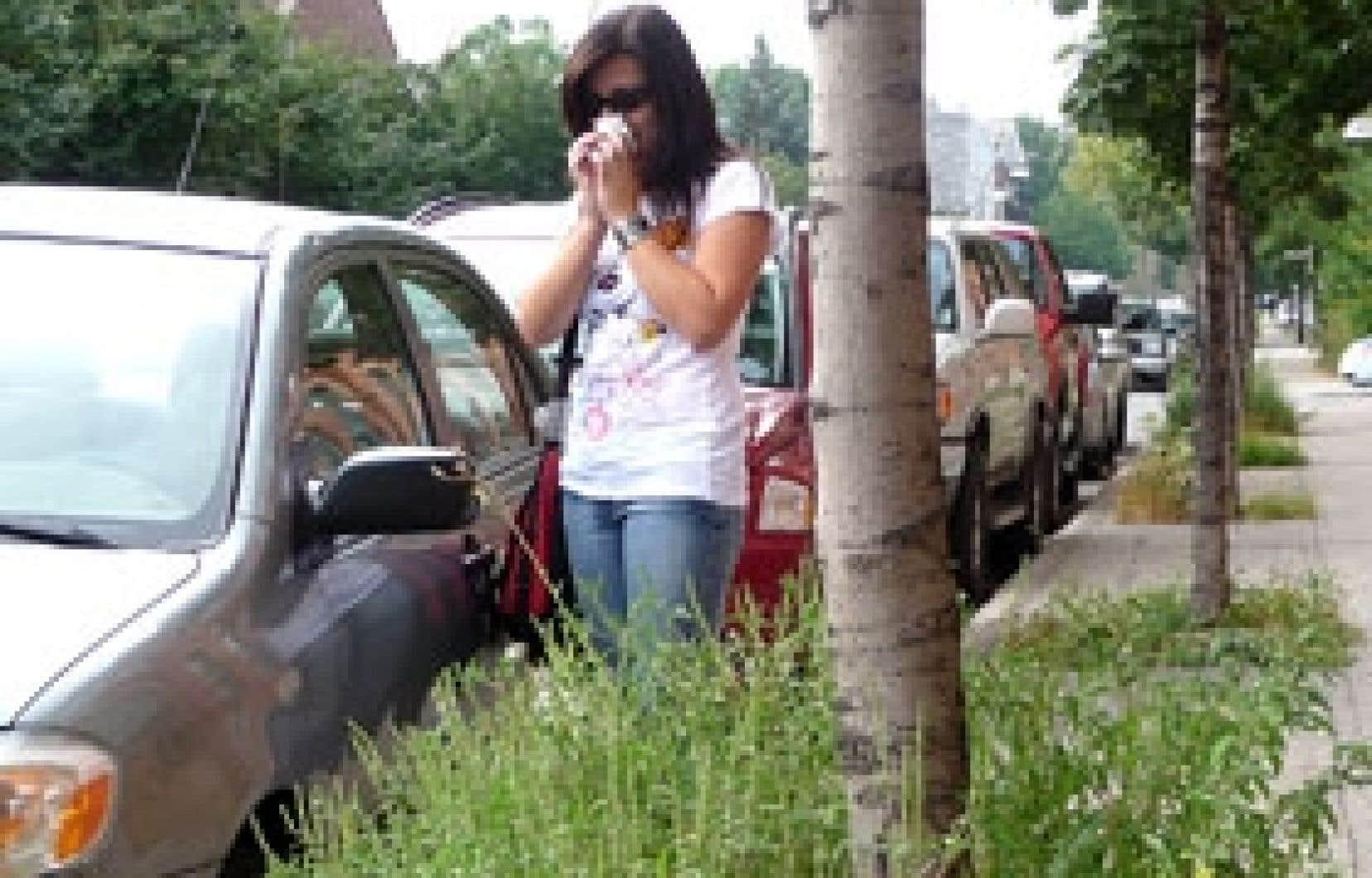 Une Montréalaise aux prises avec le rhume des foins photographiée devant l'un des bosquets où l'herbe à poux profite des engrais de la Ville de Montréal.