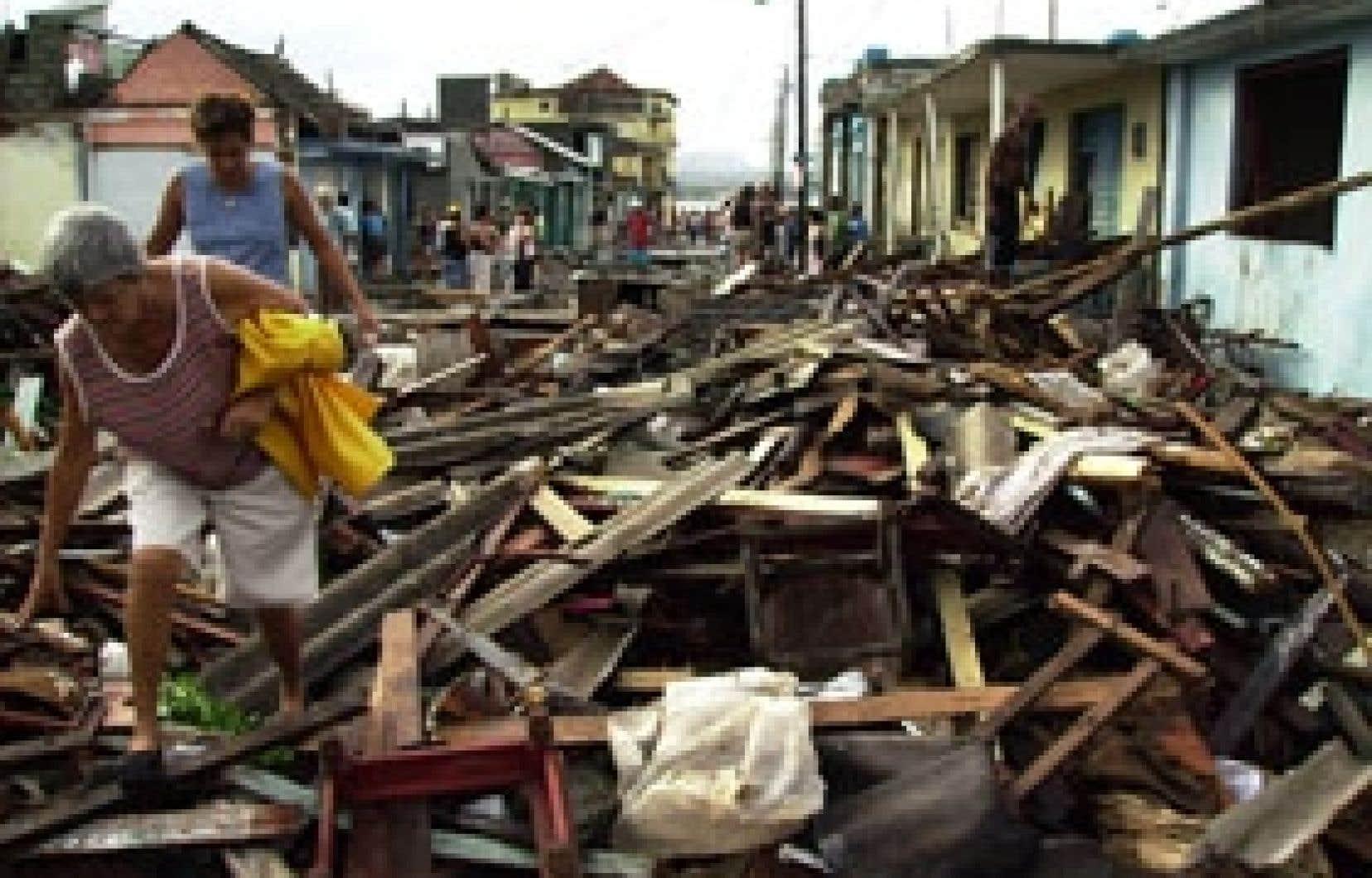 Des citoyens de Baracoa, à Cuba, tentent de se frayer un chemin à travers les débris qui jonchent le sol après le passage de l'ouragan Ike.