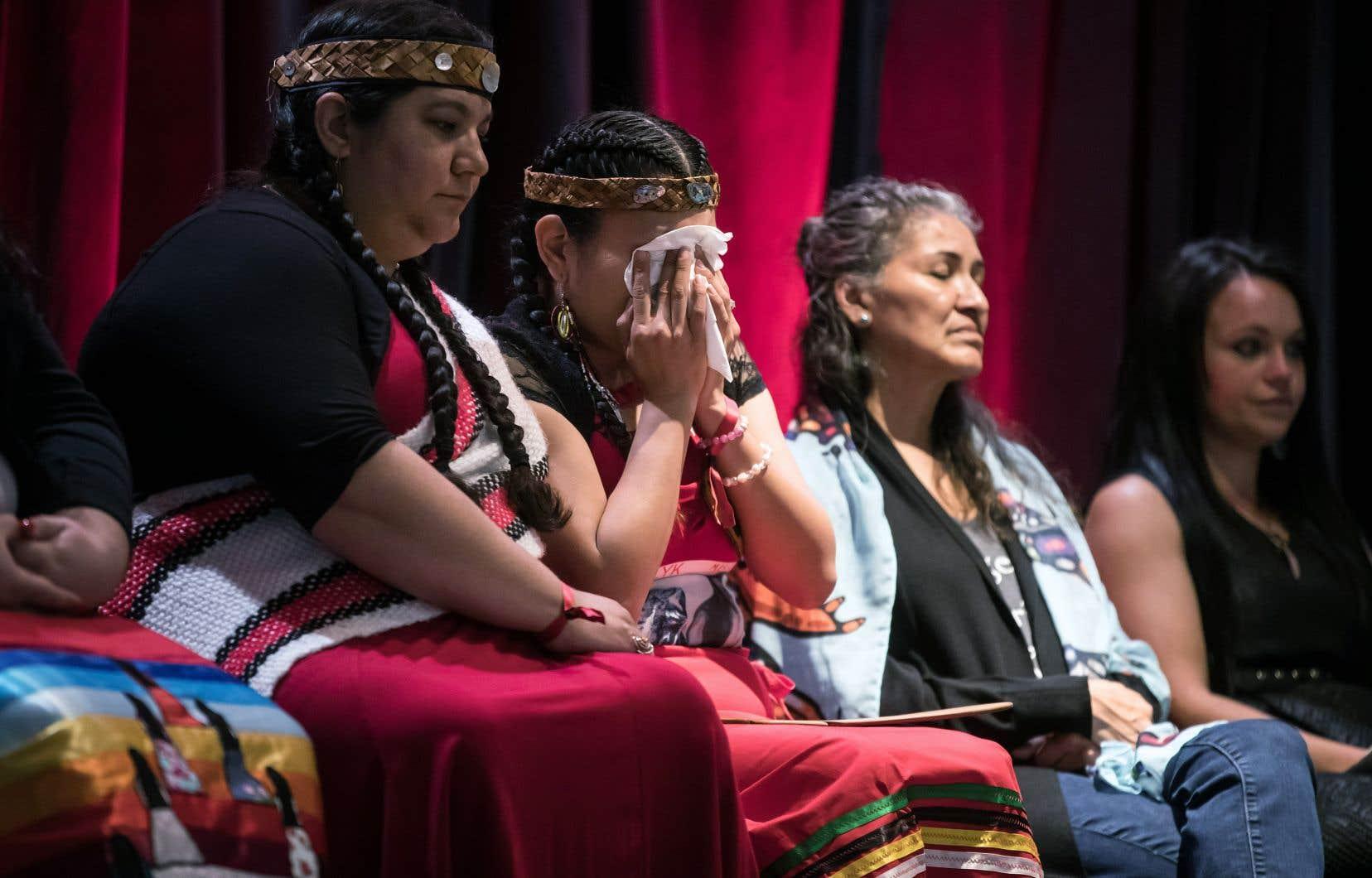 Lorelei Williams (au centre), cousine de Tanya Holyk, assassinée par le meurtrier en série Robert Pickton, essuie ses larmes après avoir écouté depuis Vancouver le reportage sur le dépôt du rapport de l'enquête sur les femmes autochtones.