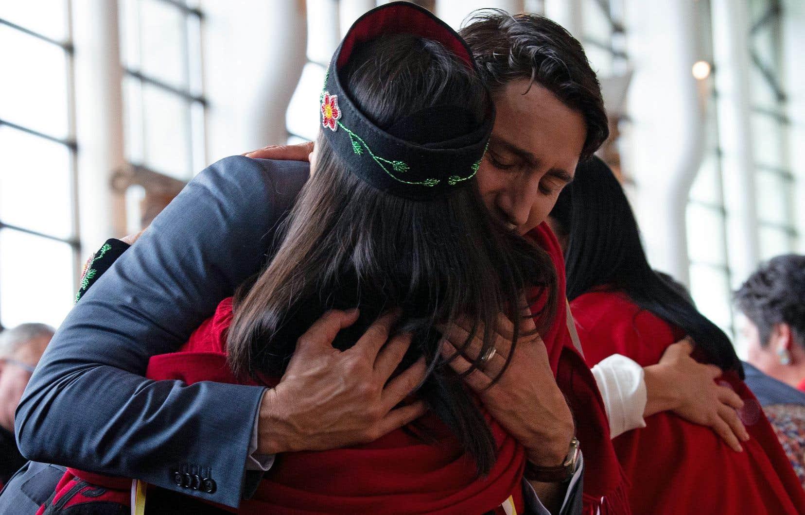 Le premier ministre Justin Trudeau fait l'accolade à une Autochtone lors de la cérémonie du dépôt du rapport d'enquête.