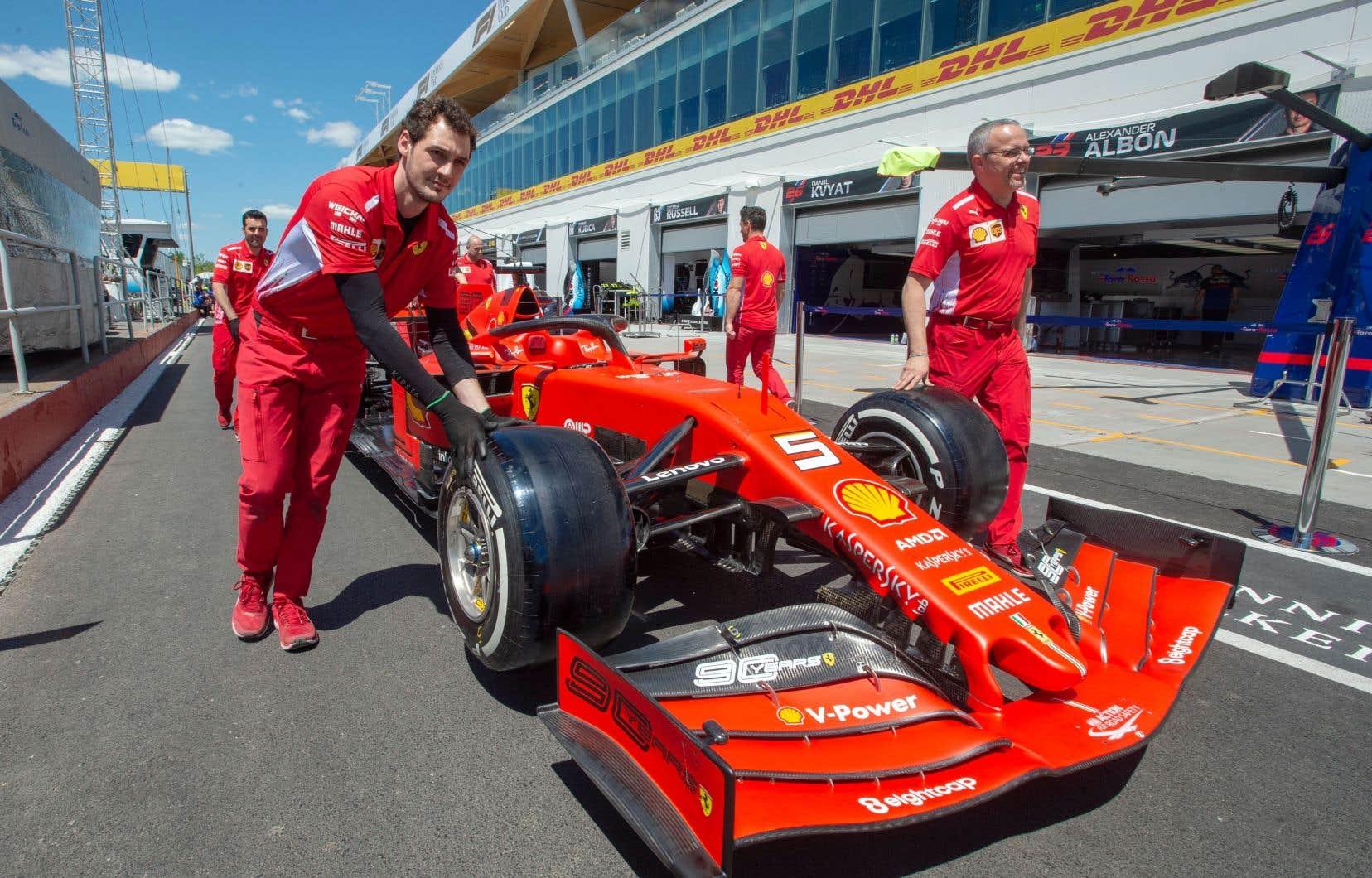 Les membres de l'équipe Ferrari déplacent la voiture de Sebastian Vettel devant les nouveaux paddocks.