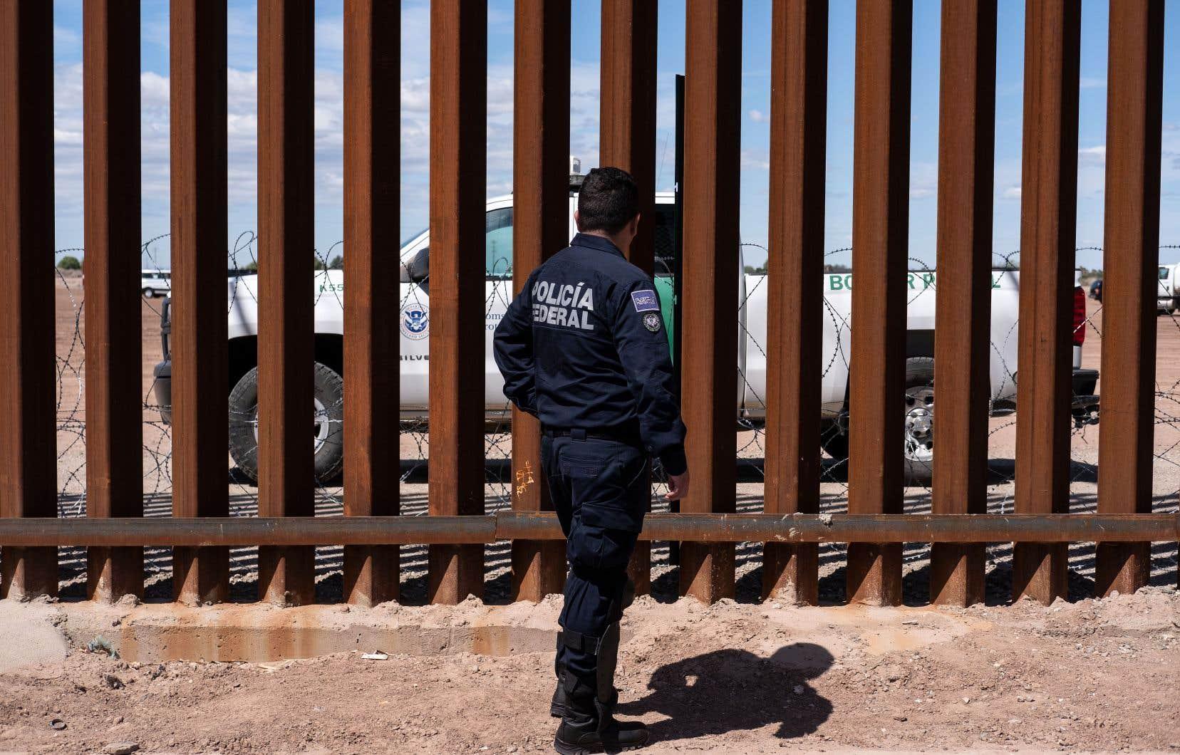 Une unité de patrouille frontalière (derrière la clôture) et un garde de la police fédérale du Mexique, aux abords de la frontière américano-mexicaine