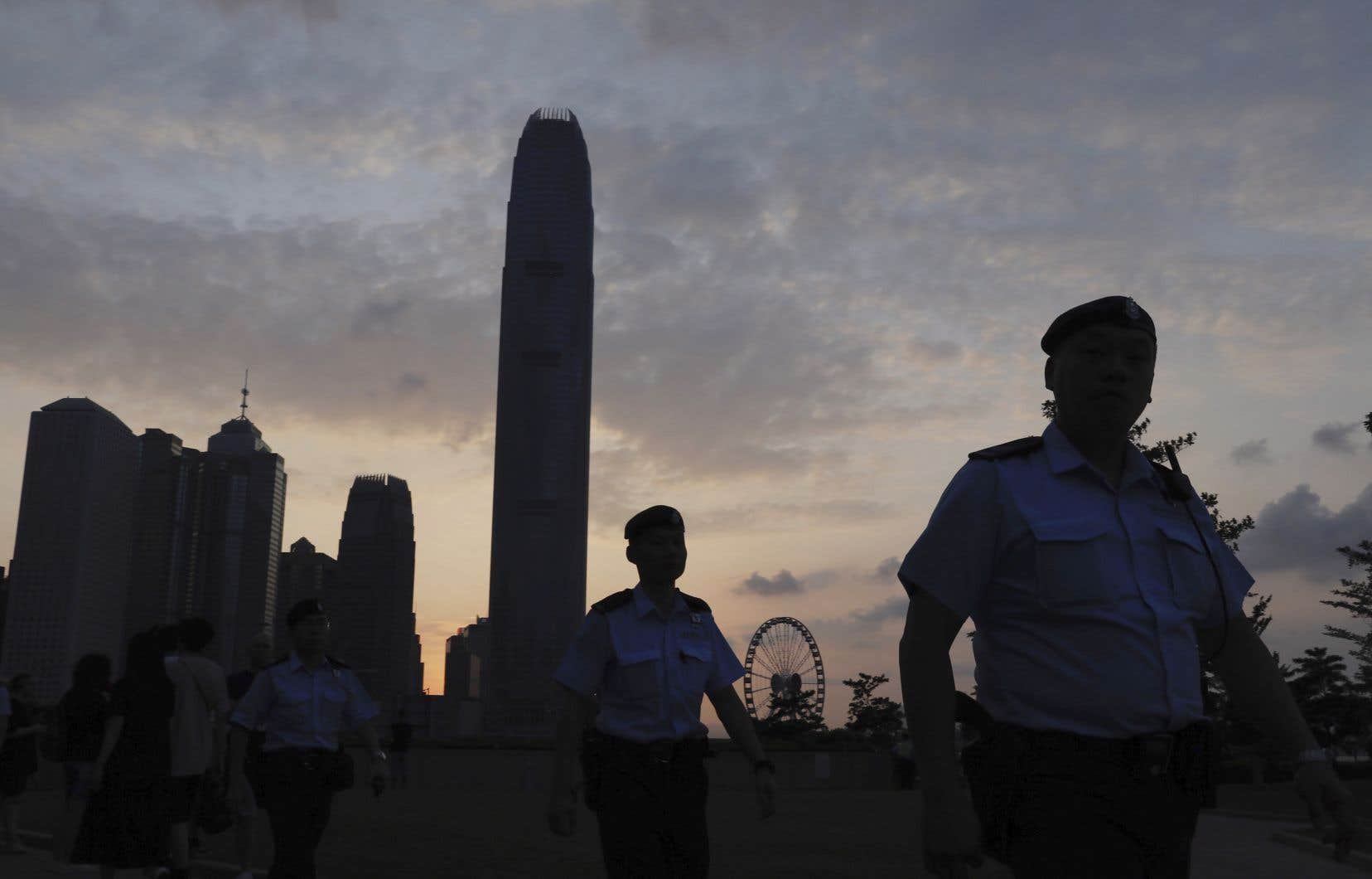 Des policiers patrouillent un parc de Hong Kong en fin de soirée, samedi.