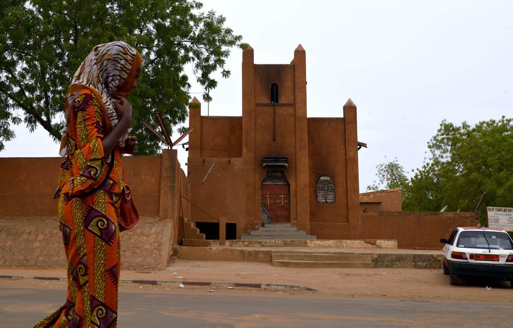 Sur cette photo datant de juin 2015, une femme marche devant l'Église Évangélique Baptiste de Niamey, qui avait aussi été la proie d'émeutes antichrétiennes en janvier de la même année.