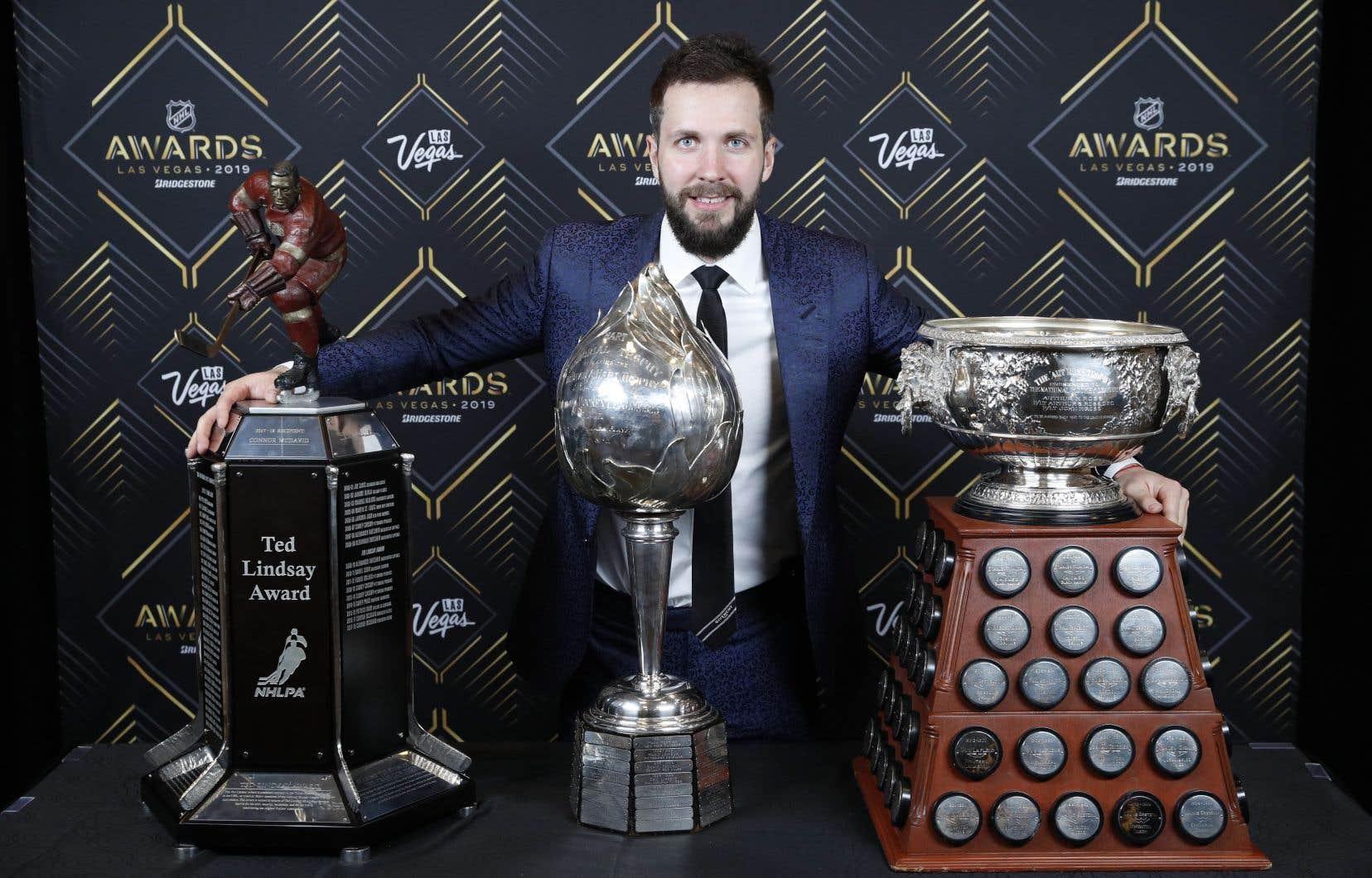 Le joueurNikita Kucherov entouré de ses trophées. De gauche à droite:les trophéesTed-Lindsay, Hart etArt-Ross.