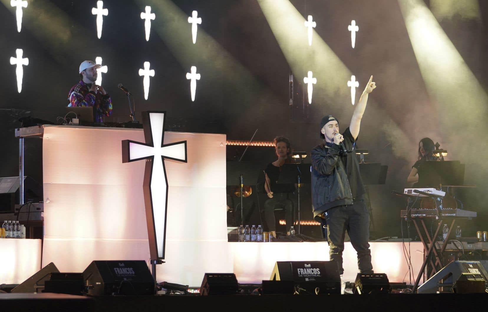 Le rappeur québécois Koriass jouaitsur scène avec DJ Manifest, juché sur une plateforme sur laquelle était installée une croix lumineuse géante.