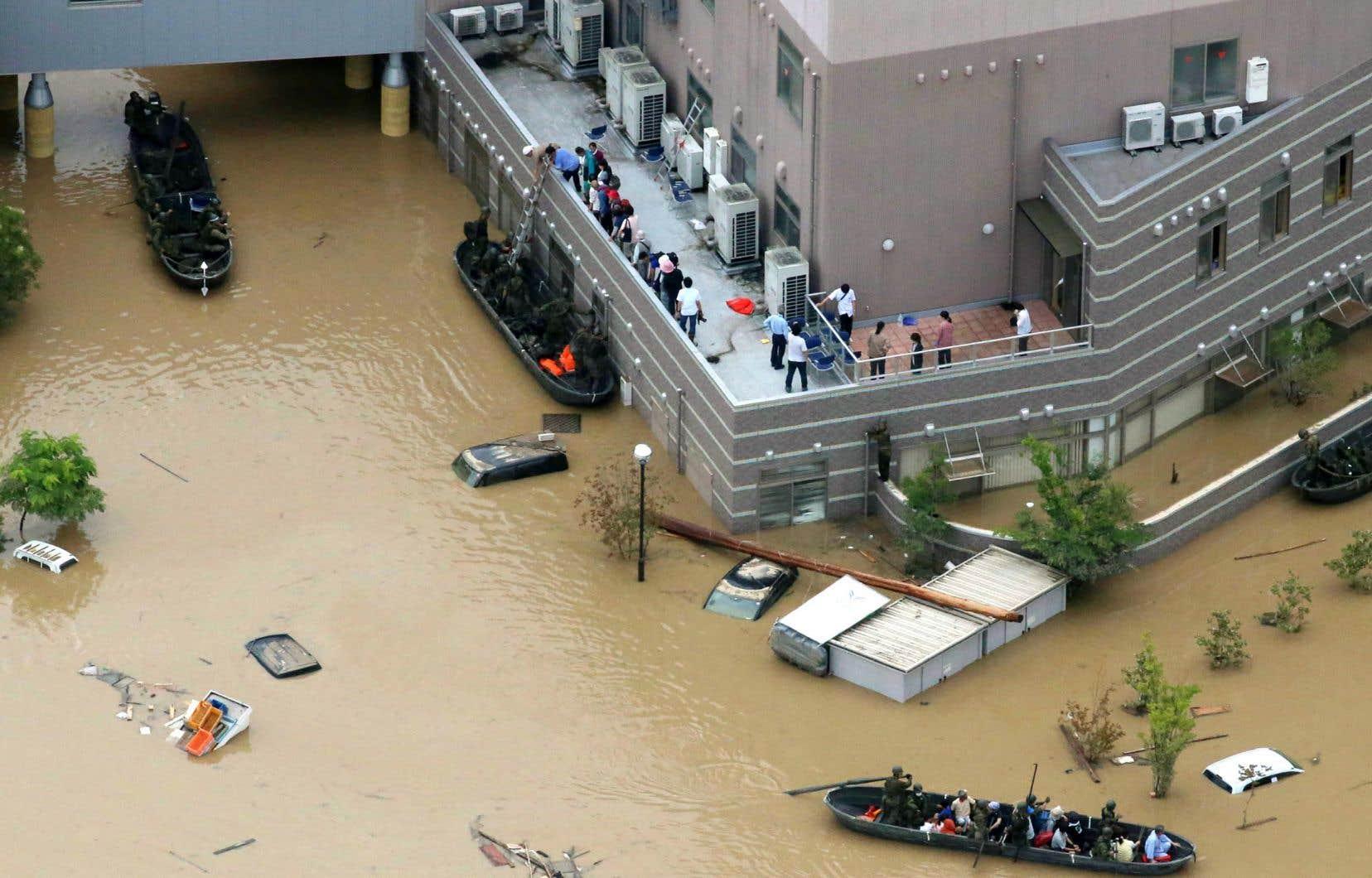 Au Japon, le fabricant japonais Hitachi prévoit des perturbations dans son réseau d'approvisionnement en Asie du Sud-Est à cause des précipitations accrues. Sur la photo, des patients sont secourus d'un hôpital après d'importantes inondations en juillet 2018.