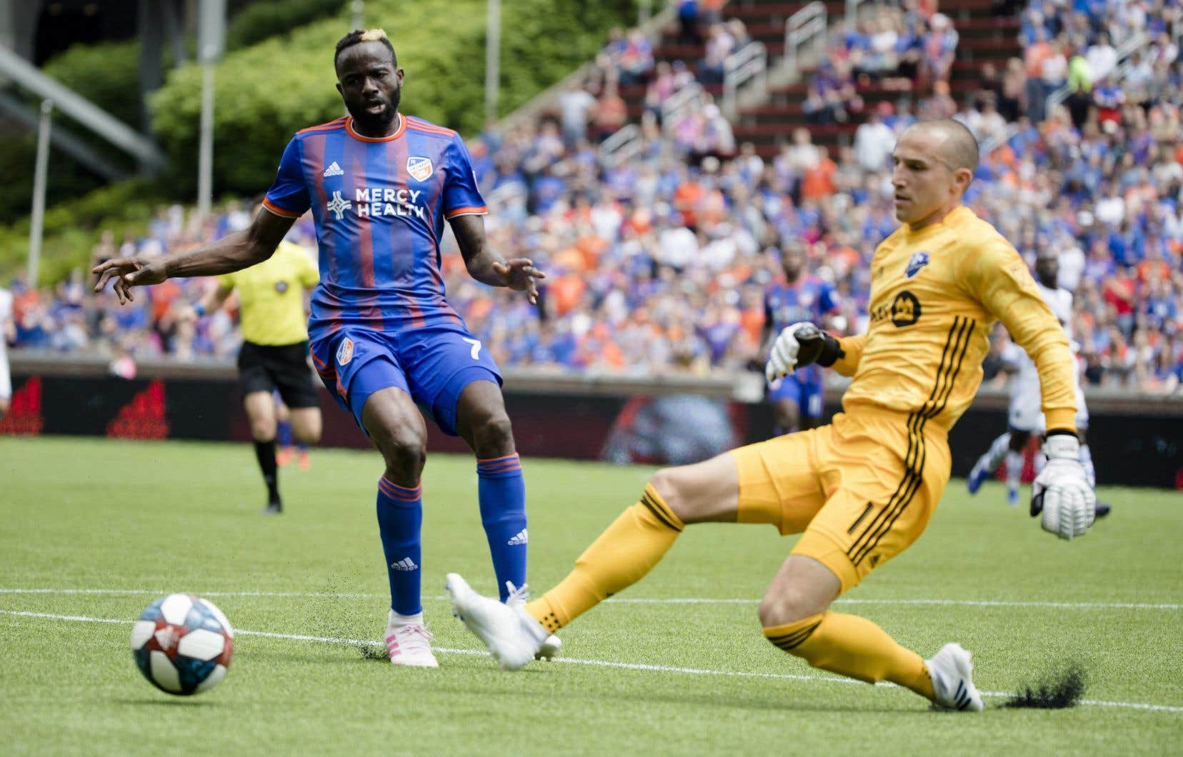 Le gardien de l'Impact de Montréal (en premier plan), Evan Bush, élimine le ballon de l'attaquant du FC Cincinnati lors d'un match de soccer de la MLS.