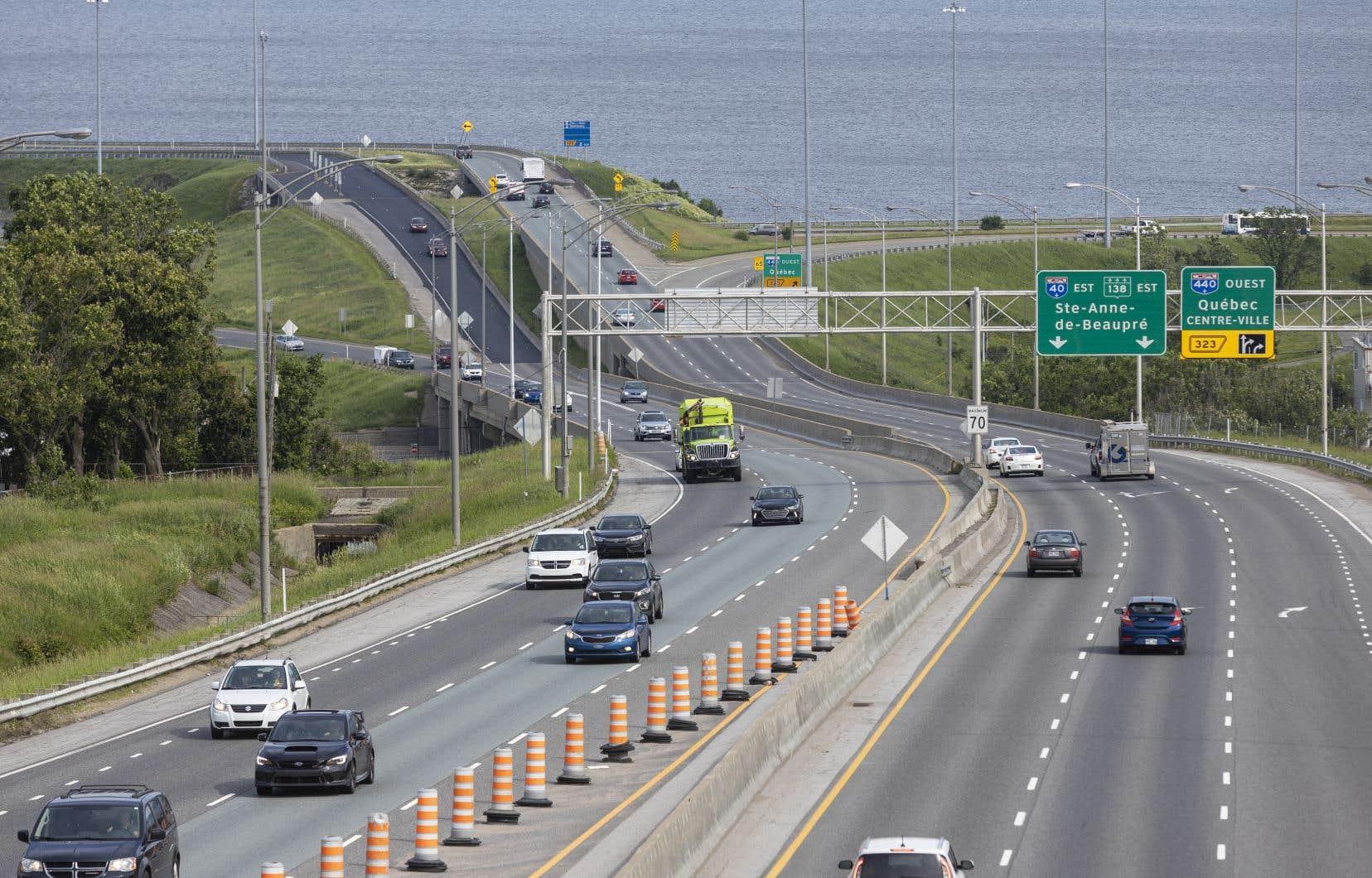 Des voitures empruntent l'autoroute 40 avec l'Île d'Orléans en arrière plan.