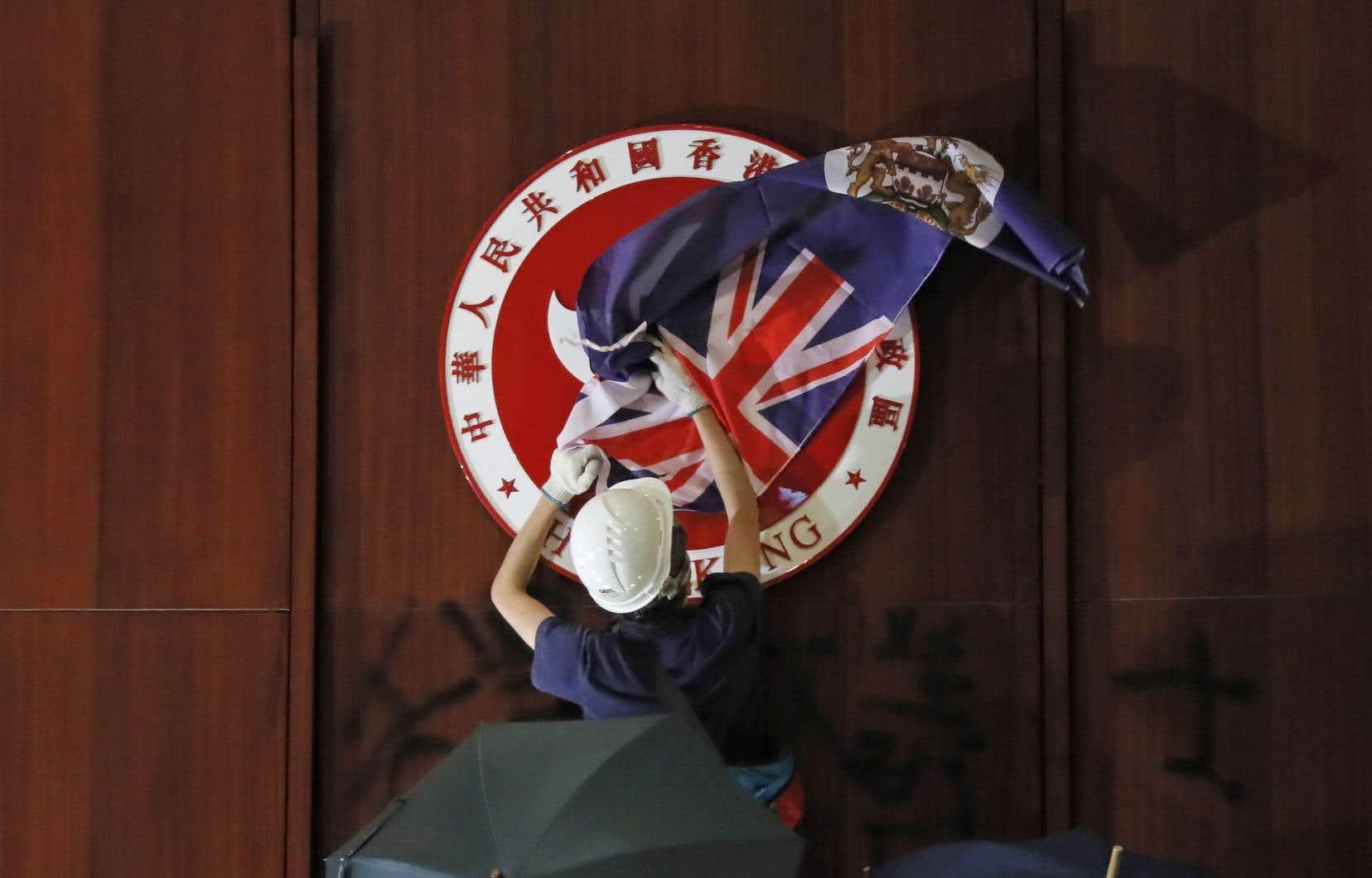 Un manifestant cache l'emblème de Hong Kong avec le drapeau colonial anglais durant l'occupation du parlement, le 1er juillet 2019.