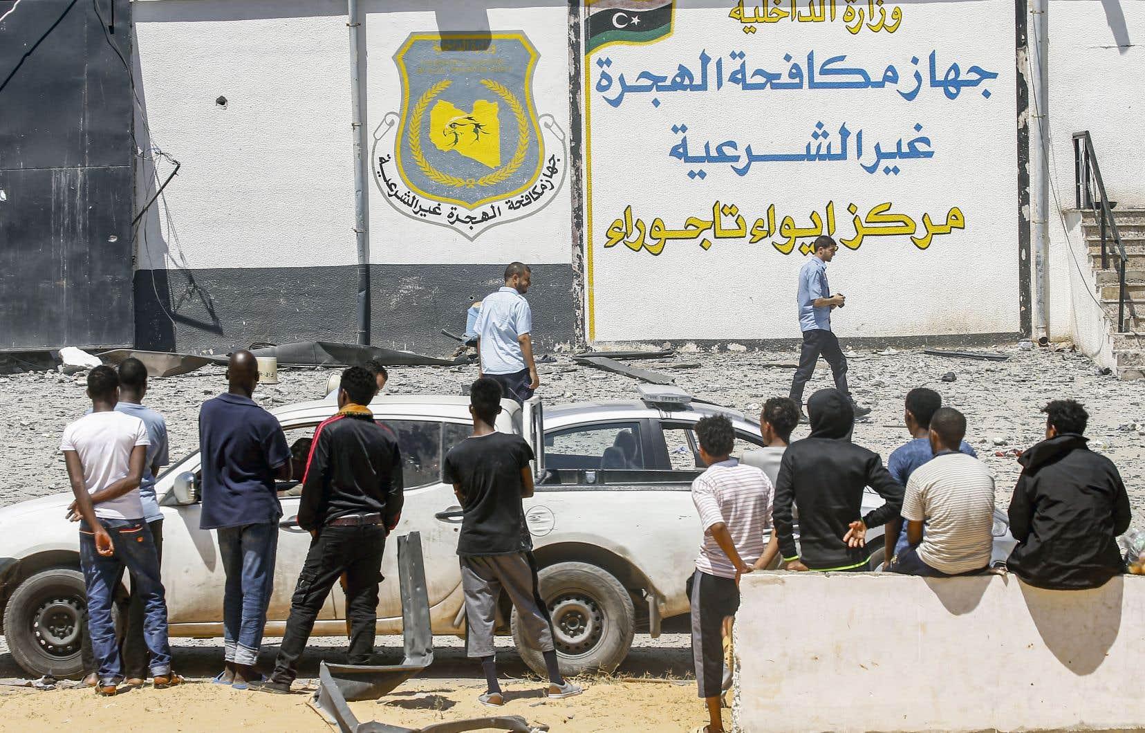 Le lendemain de la frappe meurtrière du 2 juillet, des migrants jetaient un œil sur un centre de détention du Gouvernement d'union nationale, à Tajoura.