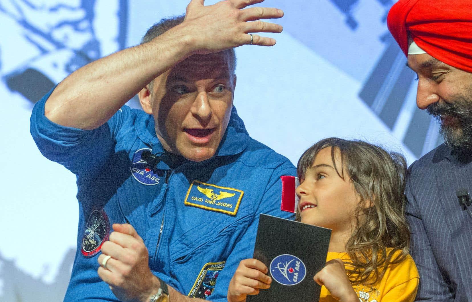 L'astronaute David Saint-Jacques a présenté quelques-uns des clichés qu'il a pris de là-haut, dans la Station spatiale internationale. Sur la photo, il est accompagné du ministre Navdeep Bains et de la petite Sophie Gentile.