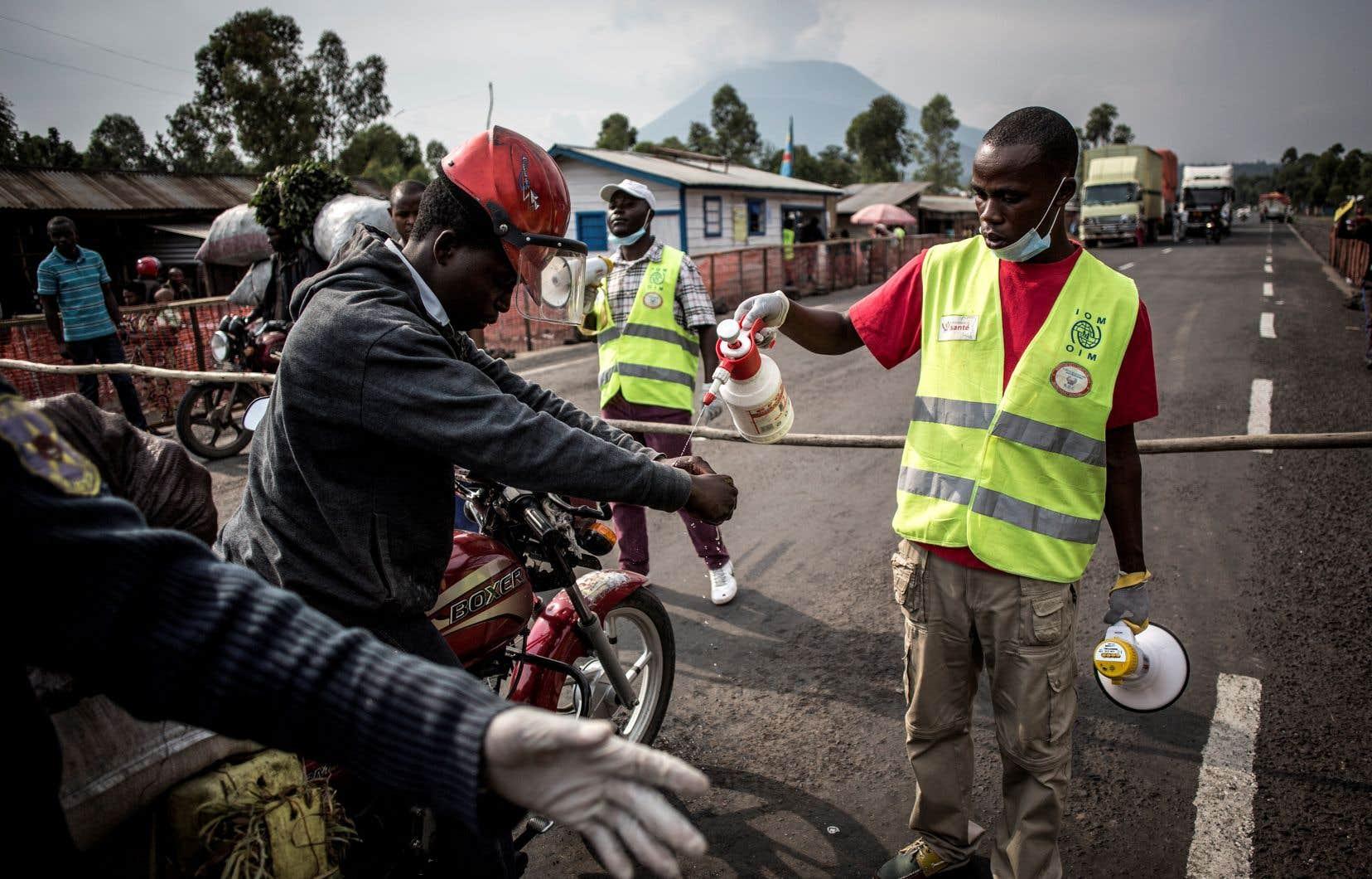 Un chauffeur de taxi motorisé se lave les mains à une station de dépistage du virus Ebola sur la route entre Butembo et Goma, le 16 juillet 2019 à Goma.