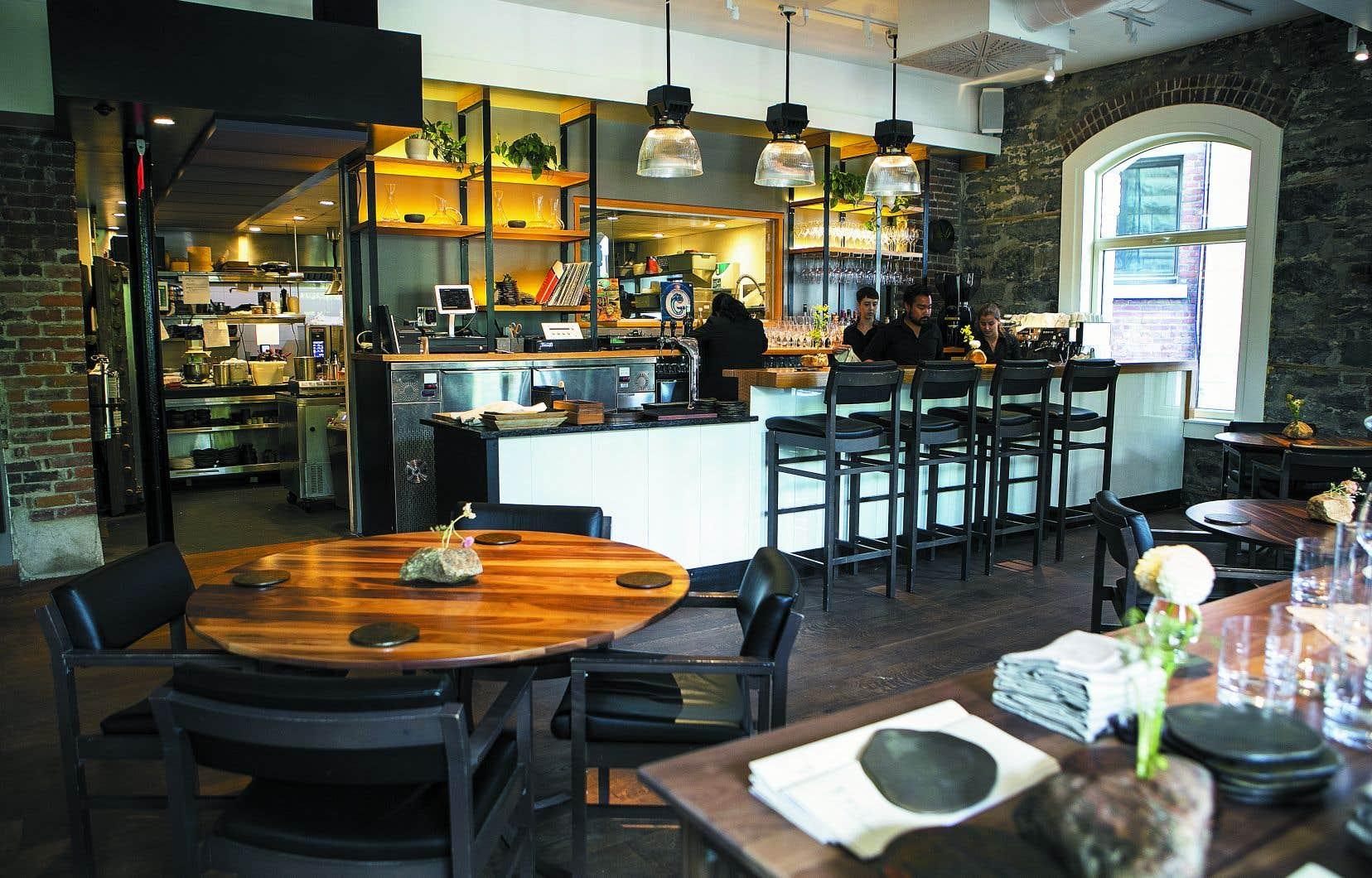 De nouvelles tables rondes en bois sont disposées au centre de la pièce de façon à accommoder non plus une cinquantaine, mais plutôt une trentaine de convives seulement.